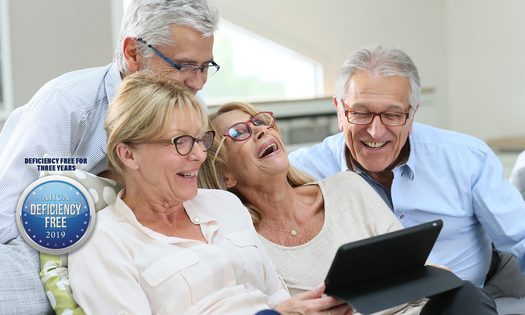 seniors laughing at something funny on a tablet