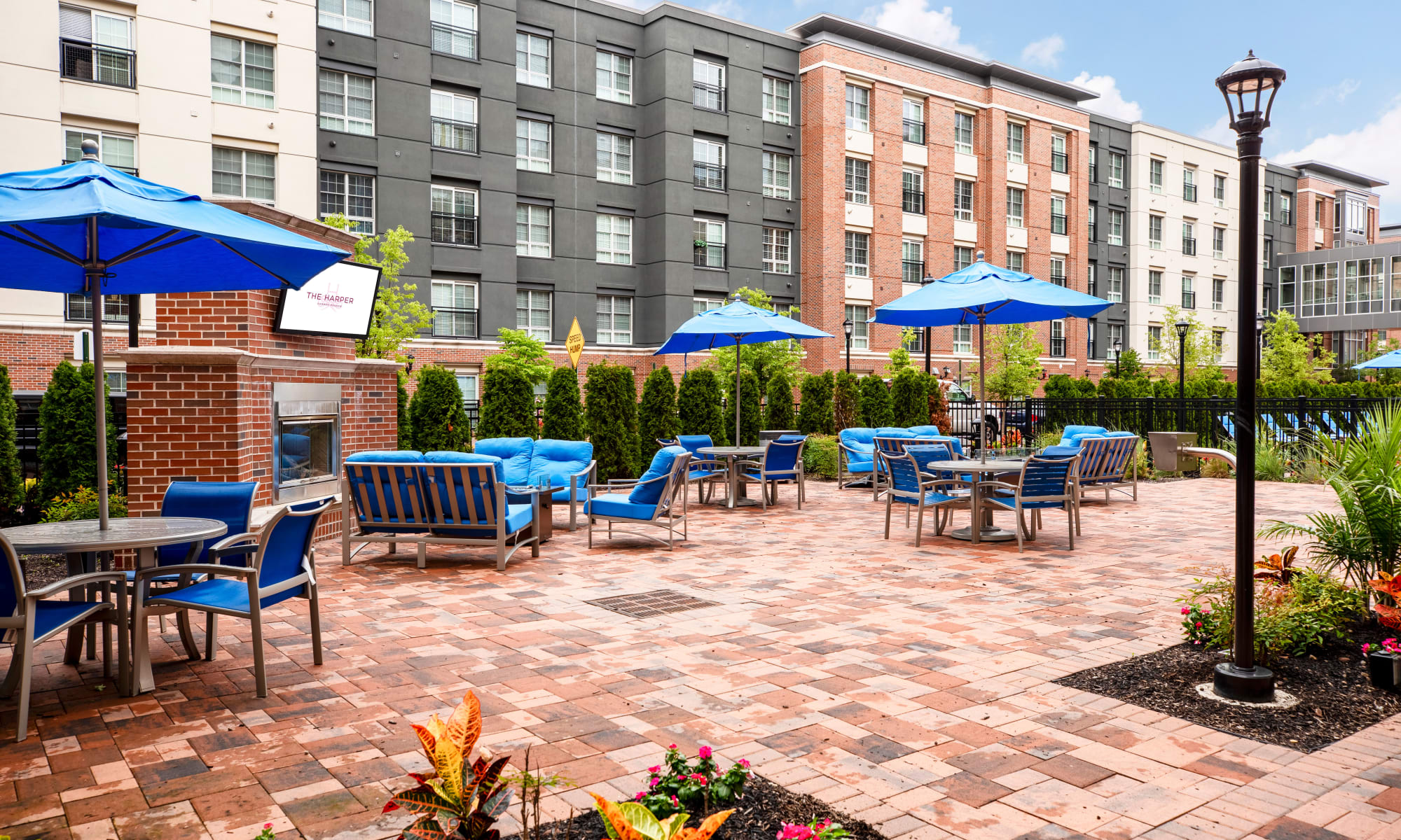 Sit by the outdoor fireplace at The Harper at Harmon Meadow in Secaucus, New Jersey