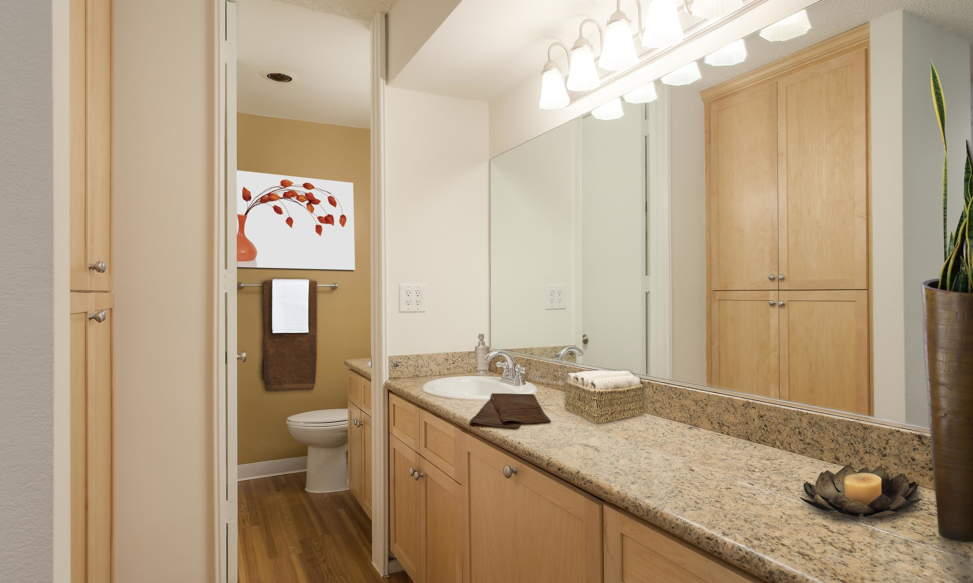 Expansive quartz countertop and an oversized vanity mirror in the primary bathroom of a model apartment at Rancho Los Feliz in Los Angeles, California