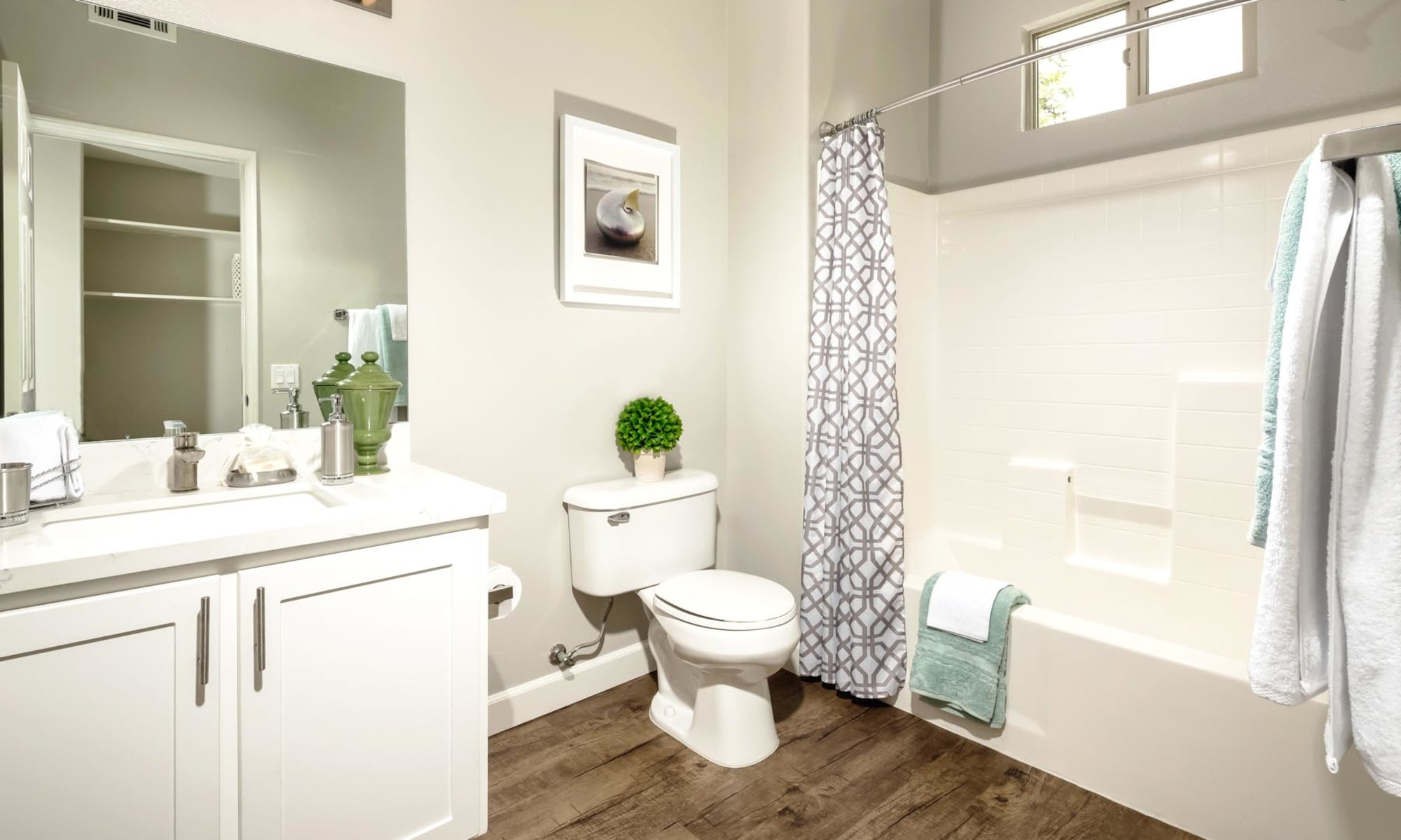 Bathroom with hardwood flooring and a tiled shower in a model home at Mission Hills in Camarillo, California