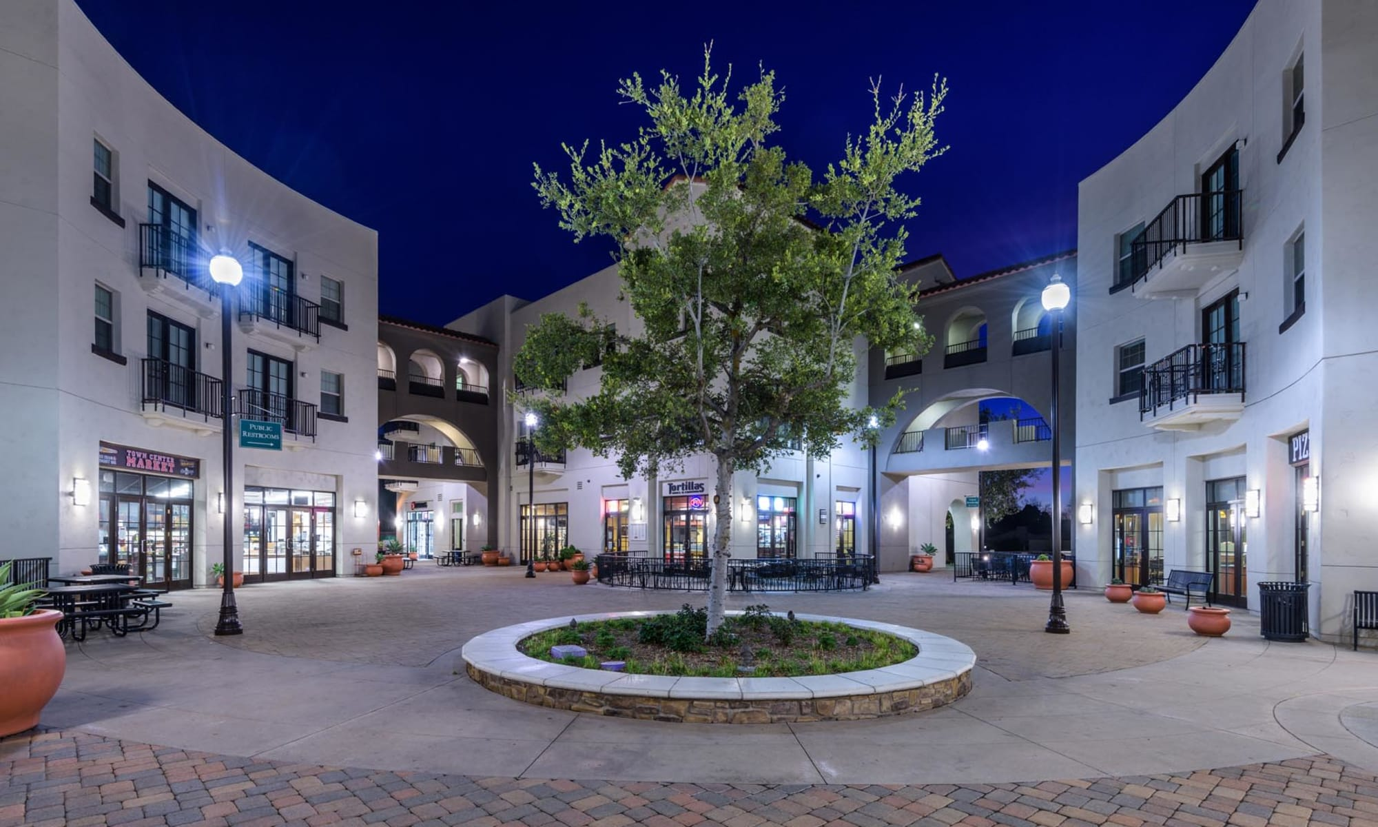 Early evening view of the courtyard with a mature tree in the center at Mission Hills in Camarillo, California