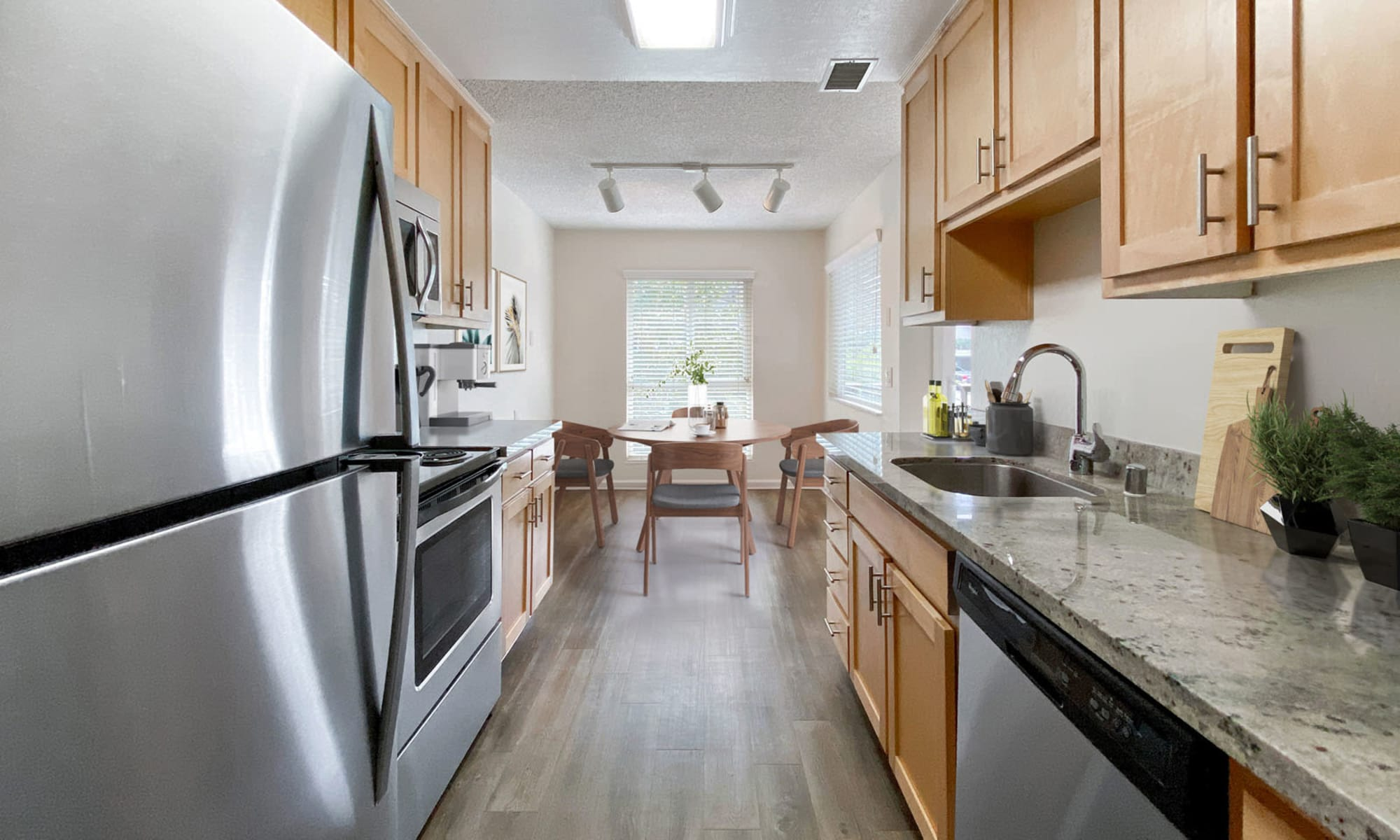 Stainless-steel appliances and granite countertops in a model home's kitchen at Pleasanton Glen Apartment Homes in Pleasanton, California