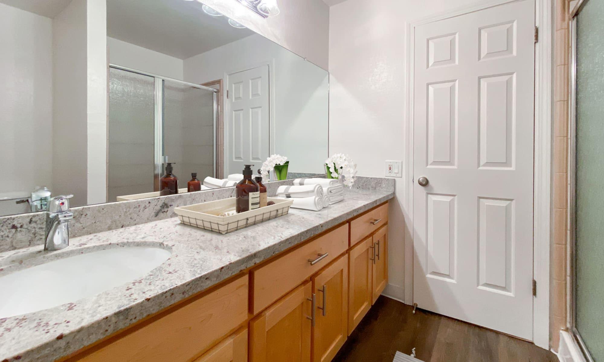 Large vanity mirror and a granite countertop in a model apartment's primary bathroom at Pleasanton Glen Apartment Homes in Pleasanton, California