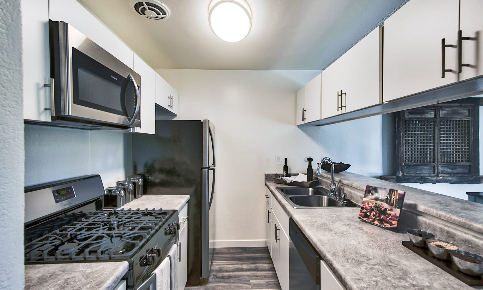 Hardwood flooring and granite countertops in a model apartment's kitchen at Mediterranean Village Apartments in Costa Mesa, California