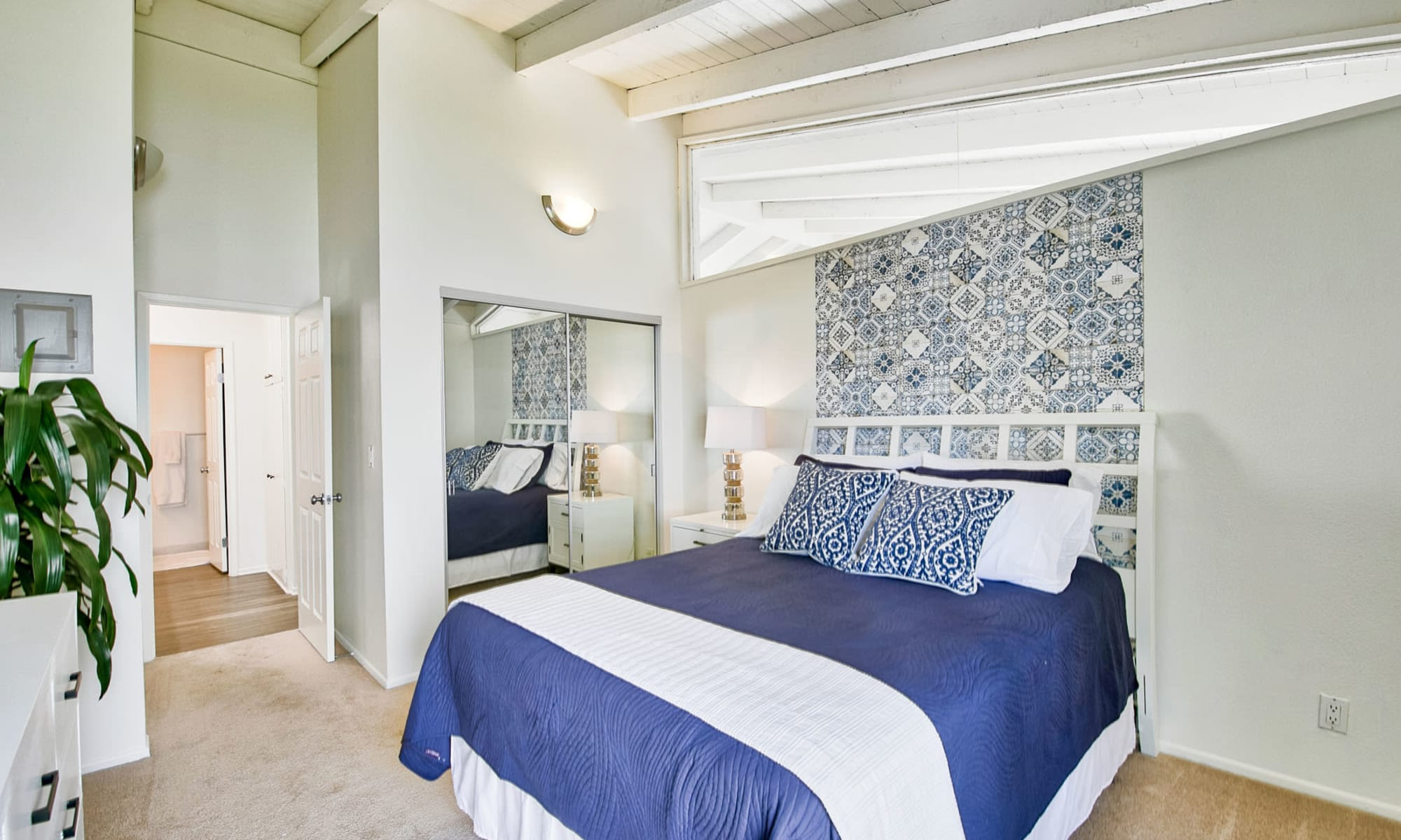 Model apartment's primary bedroom with a vaulted ceiling and plush carpeting at Mediterranean Village Apartments in Costa Mesa, California