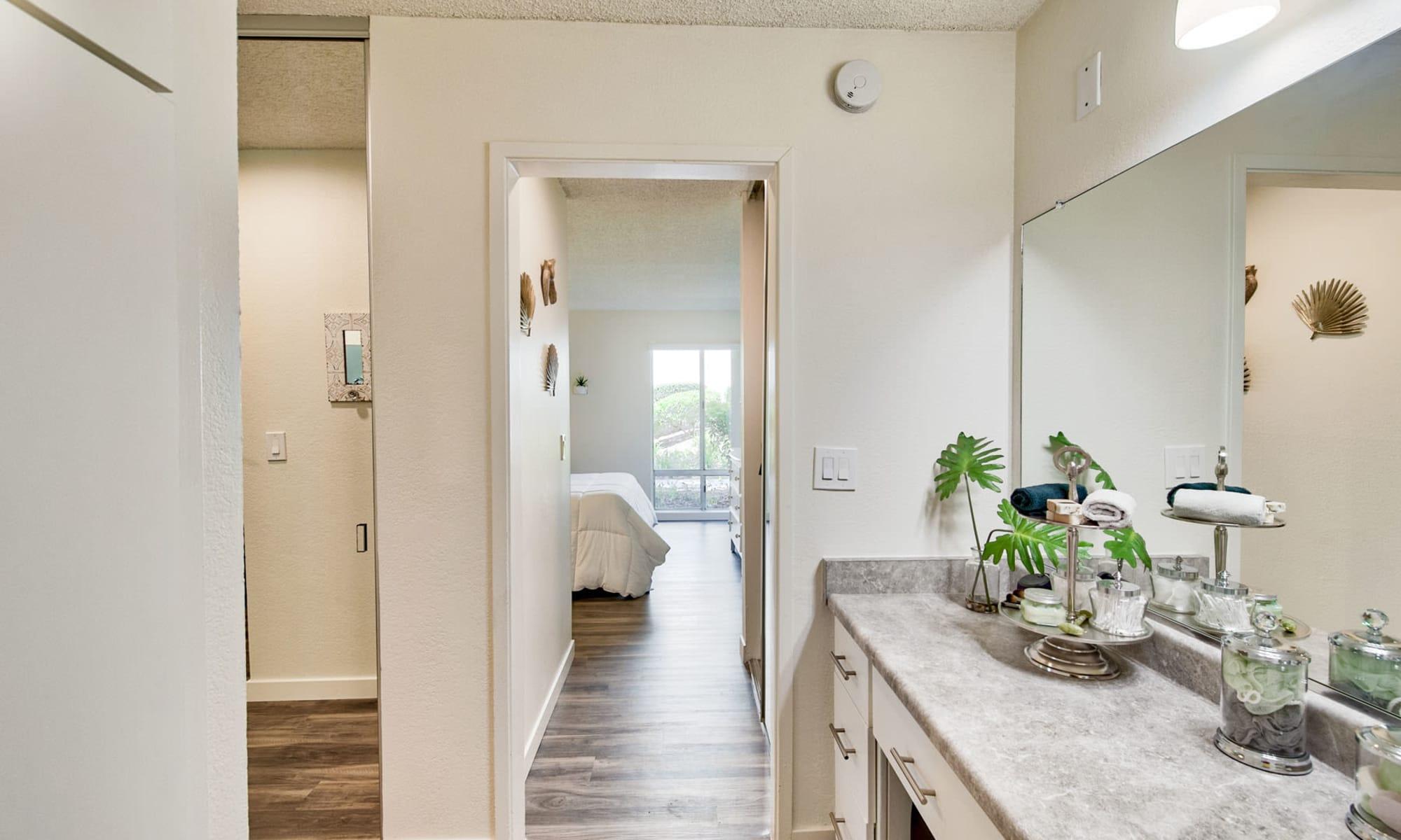 En suite bathroom with granite countertops in a model home's primary bedroom at Mediterranean Village Apartments in Costa Mesa, California
