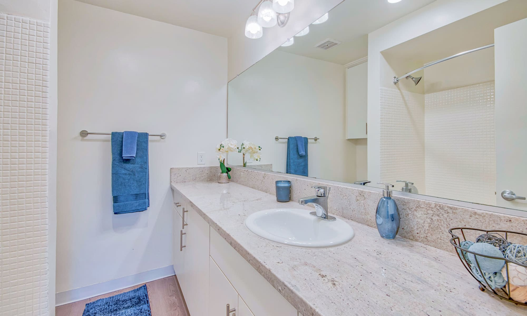 Ample countertop space and a large vanity mirror in a model home's bathroom at Villa Vicente in Los Angeles, California