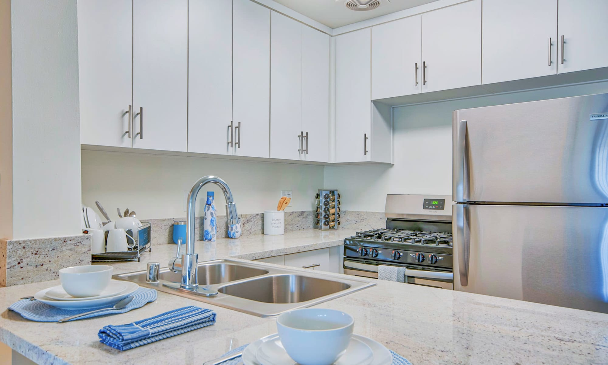 Spacious one bedroom home's kitchen with granite countertops and stainless-steel appliances at Villa Vicente in Los Angeles, California