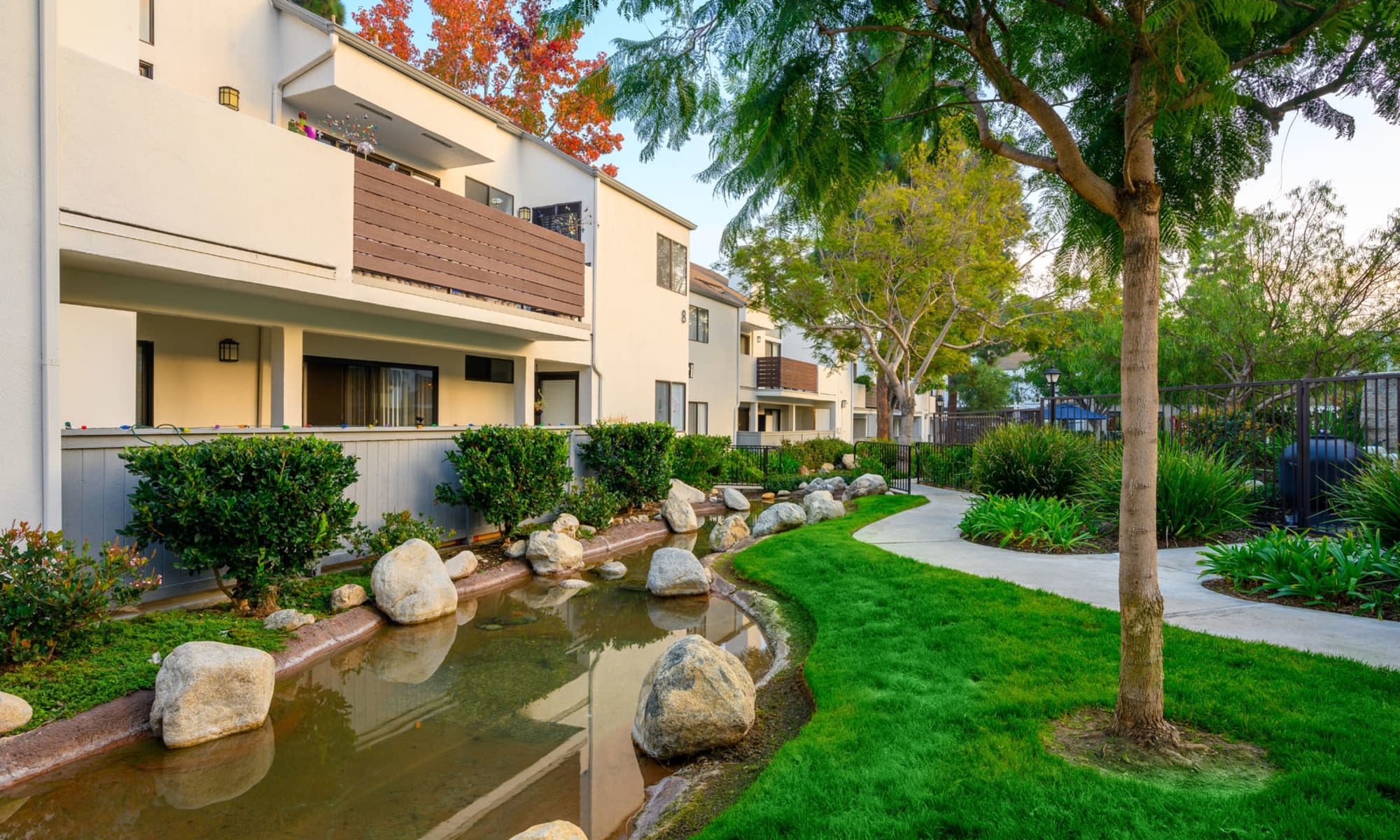 A small pond, green grass, and mature trees outside resident buildings at Sendero Huntington Beach in Huntington Beach, California