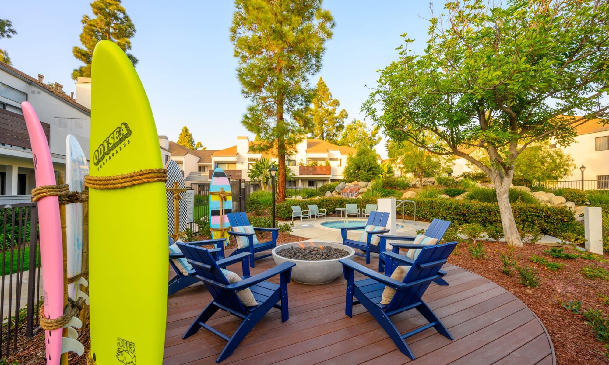 Surfboards and Adirondack chairs around the fire pit at Sendero Huntington Beach in Huntington Beach, California