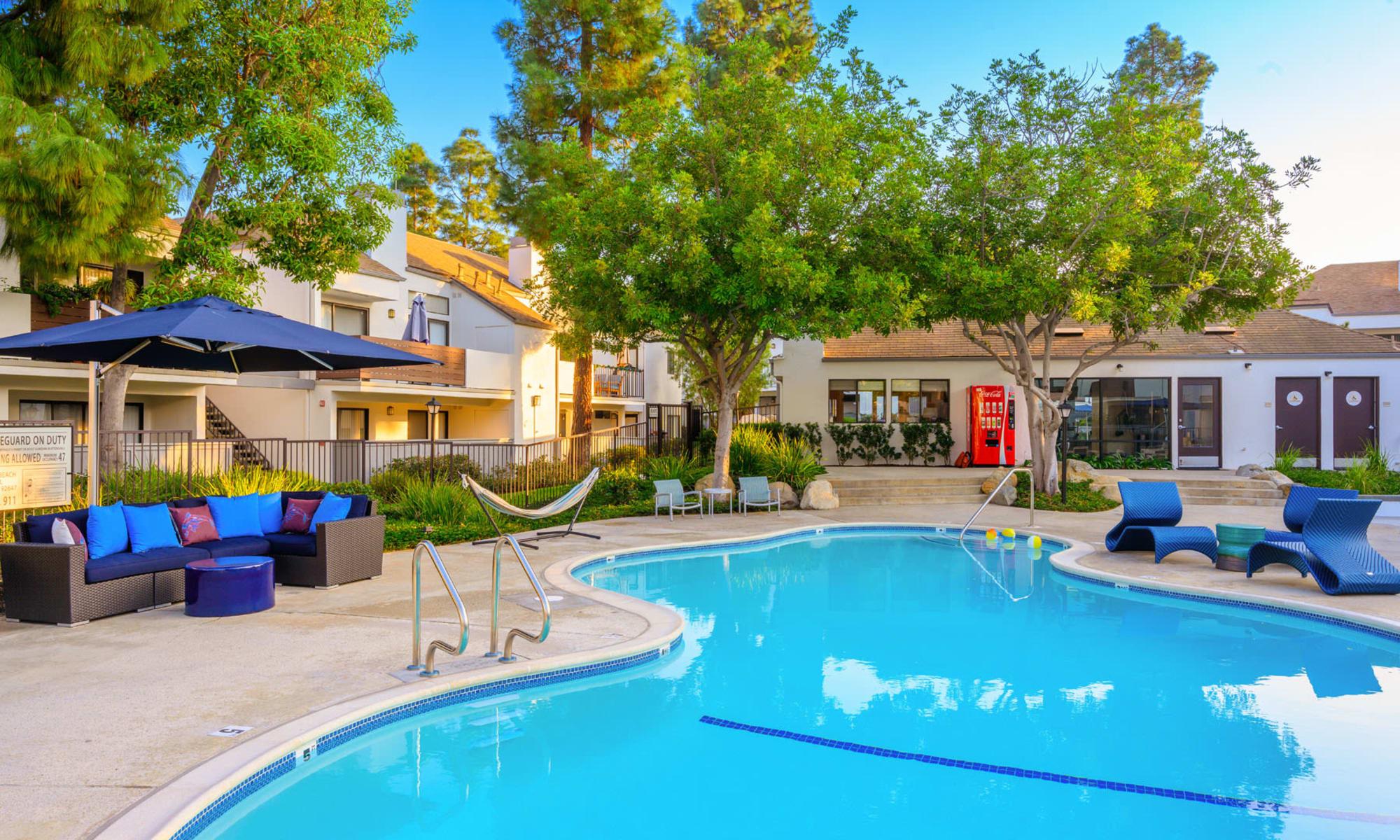 Shaded lounge areas near the swimming pool surrounded by mature trees at Sendero Huntington Beach in Huntington Beach, California