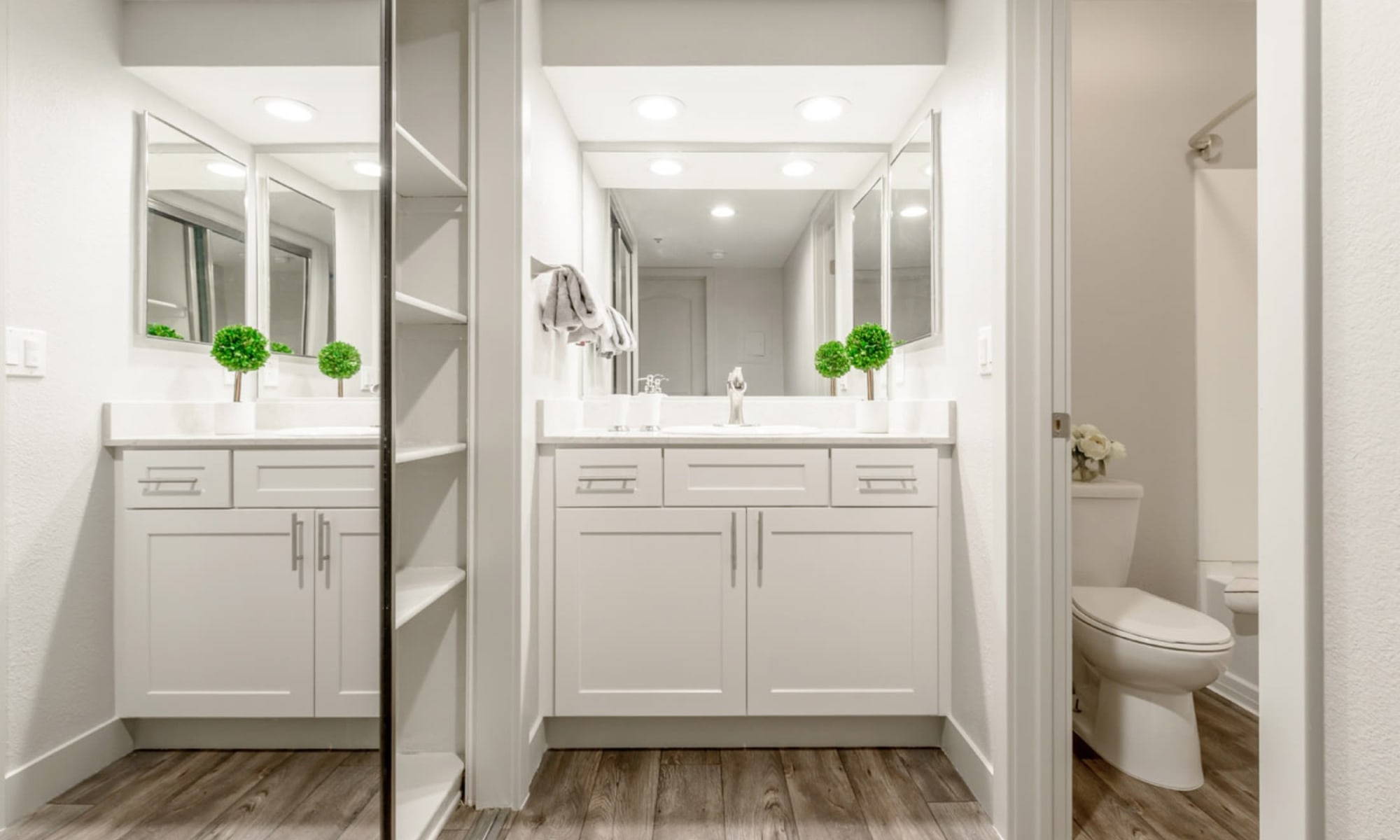 Bathroom with a large vanity mirror and sleek quartz countertop in a remodeled apartment at Sendero Huntington Beach in Huntington Beach, California