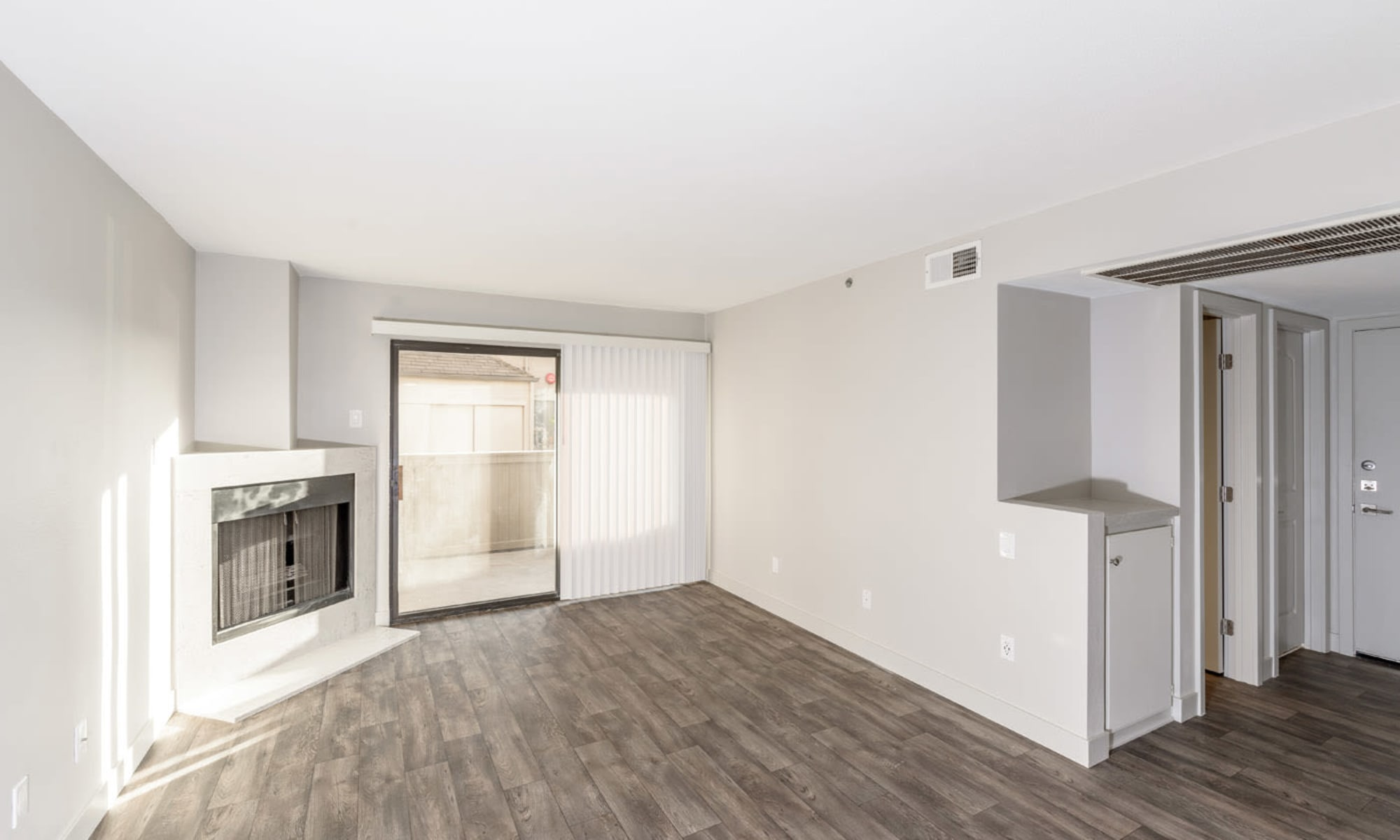 Hardwood-style flooring and ceiling fan in the dining and kitchen areas in a model apartment at Sendero Huntington Beach in Huntington Beach, California