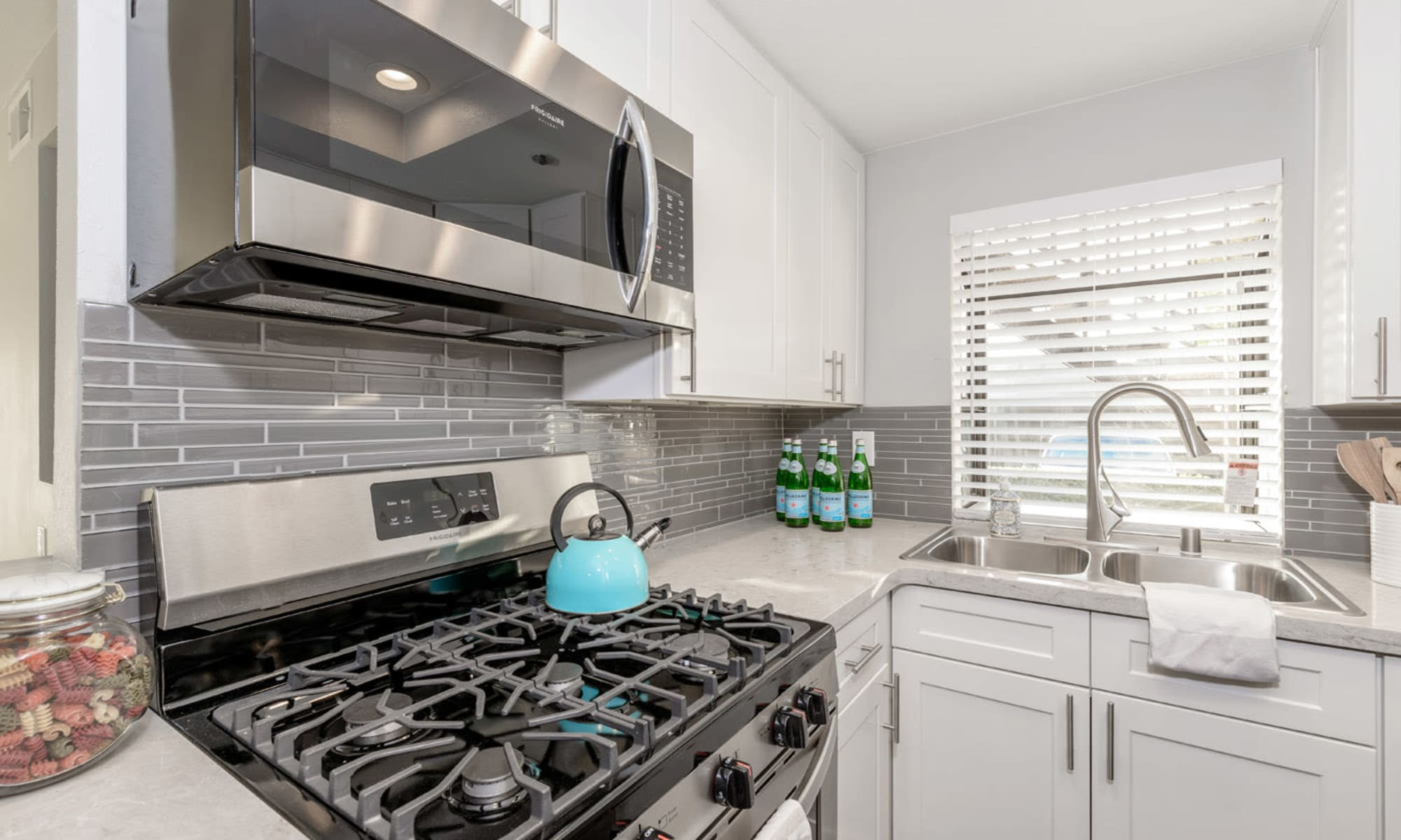 Subway tile backsplash and stainless-steel appliances in a remodeled model home's kitchen at Sendero Huntington Beach in Huntington Beach, California