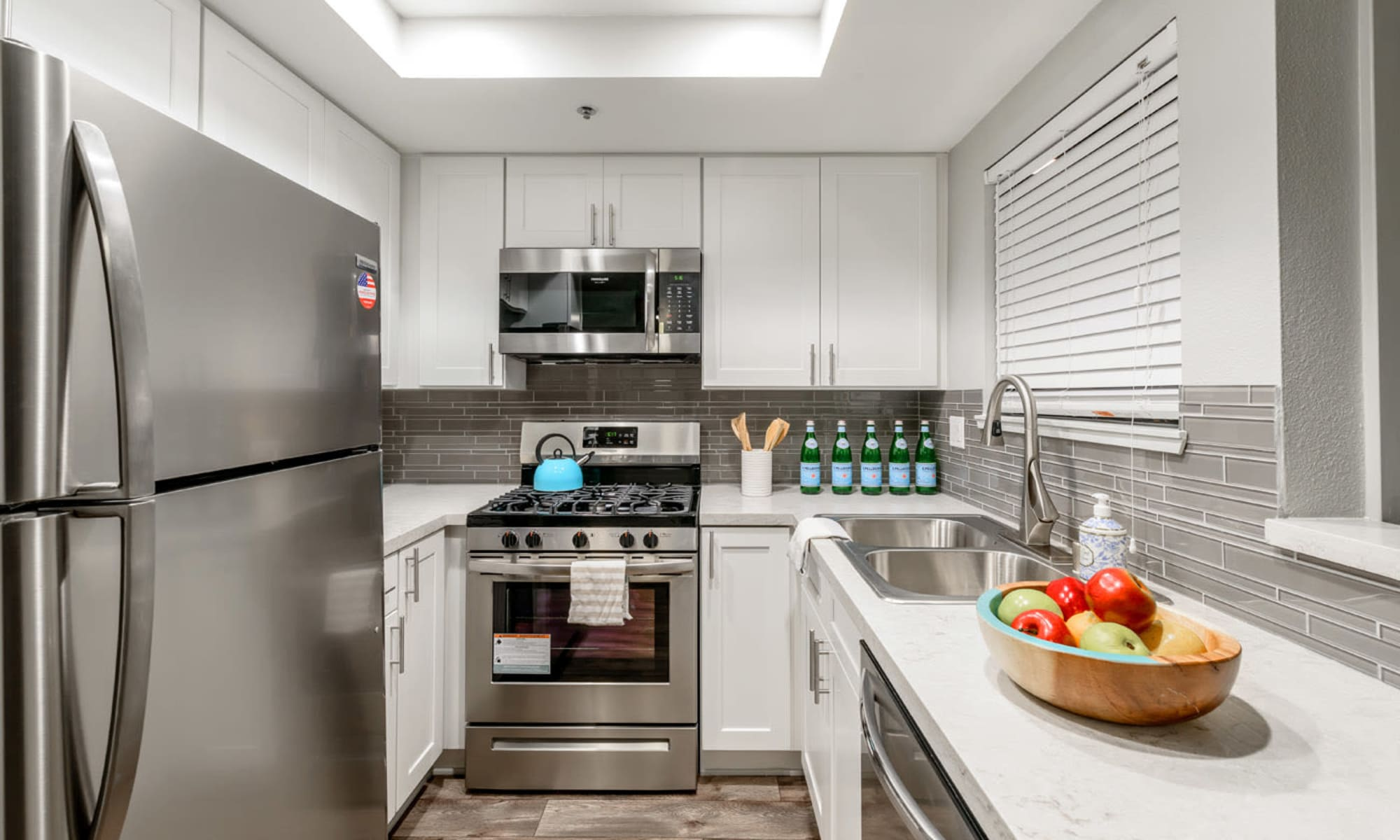 Sleek and modern kitchen with a yummy bowl of fruit on the counter for a quick snack at Sendero Huntington Beach in Huntington Beach, California