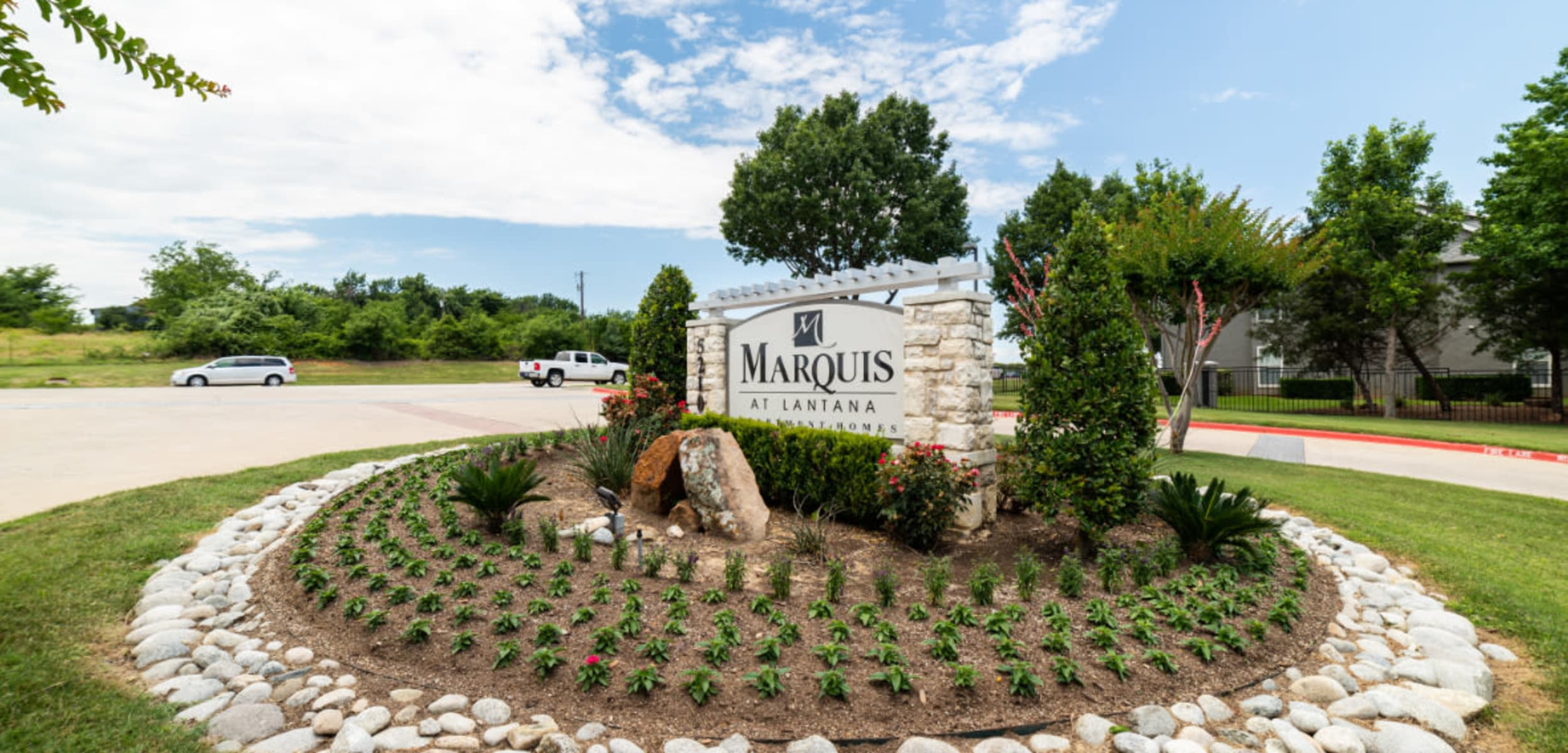Property stone signage with plants at Marquis at Lantana in Flower Mound Texas