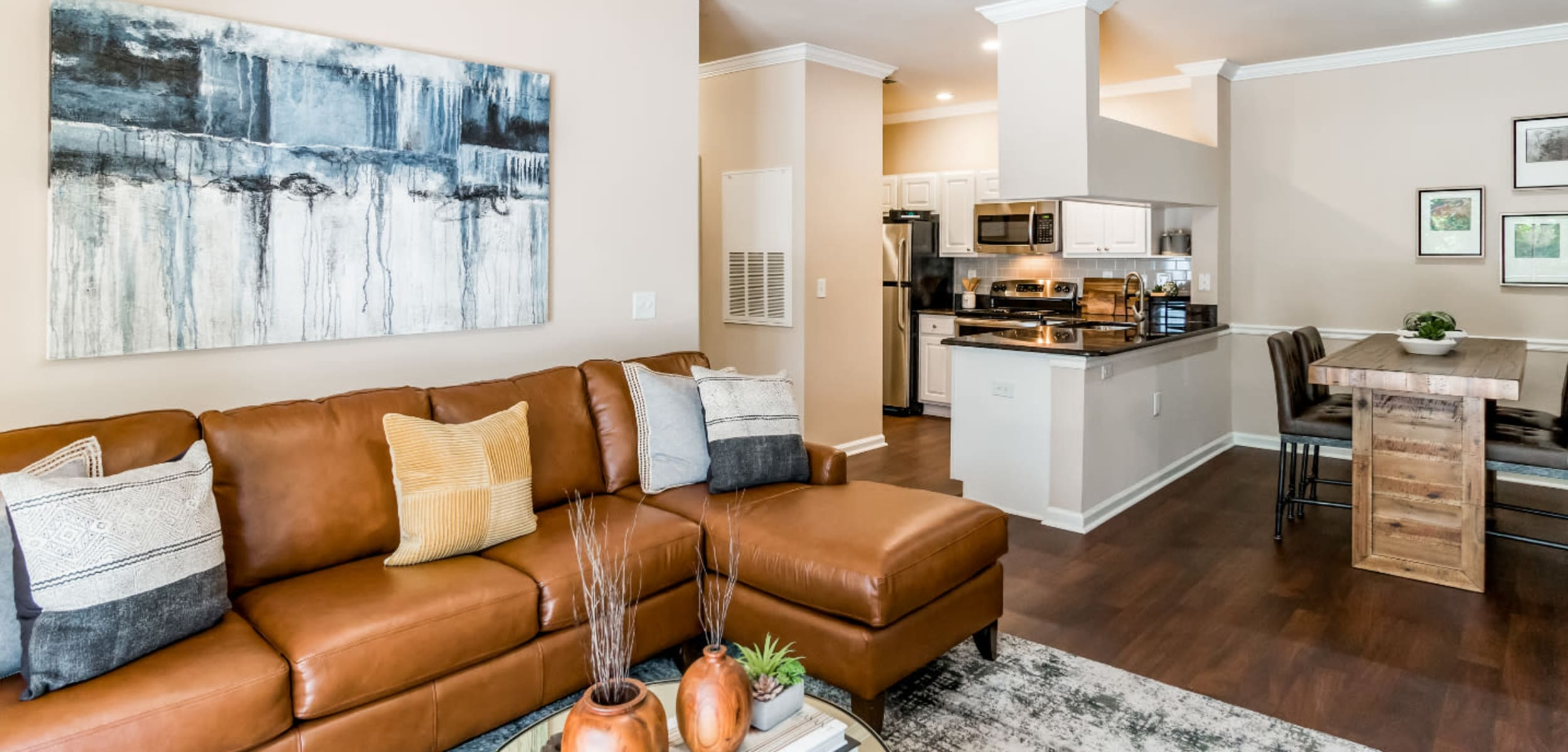 Spacious living area with modest dining area and wood flooring at Marquis at Carmel Commons in Charlotte, North Carolina