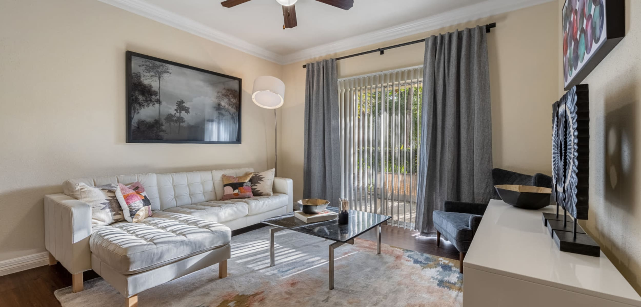 Modern and sleek living room with large rug on wood floor at Marquis at Kingwood in Kingwood, Texas
