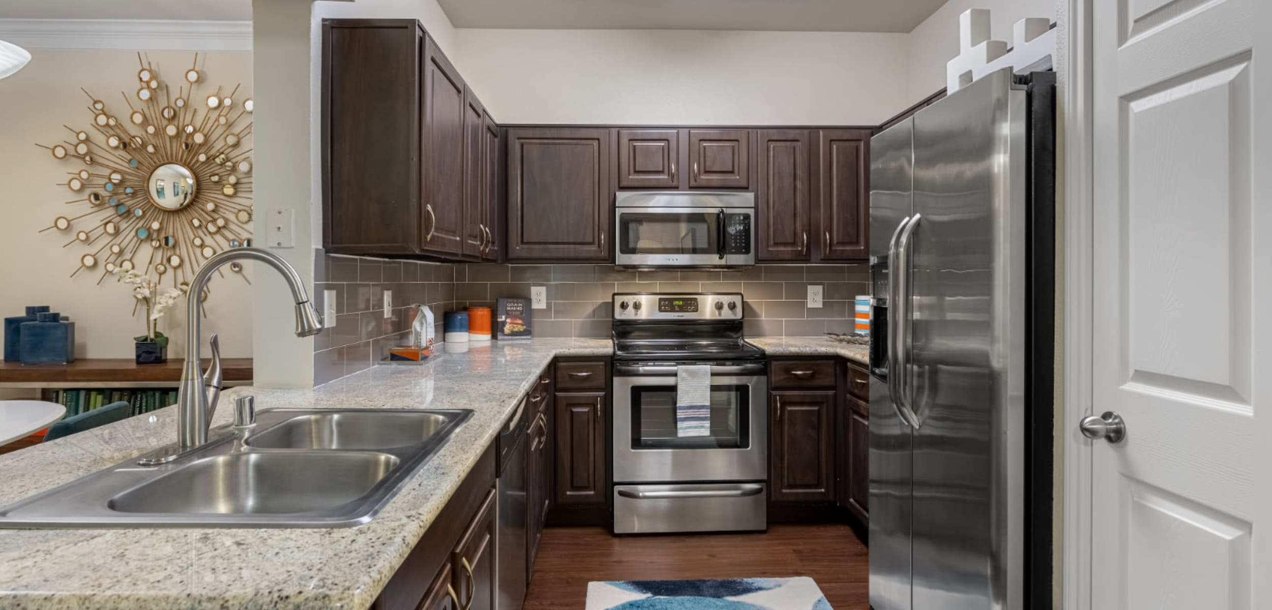 Modern kitchen with granite counters, stainless steel appliances, and wood flooring at Marquis at Kingwood in Kingwood, Texas