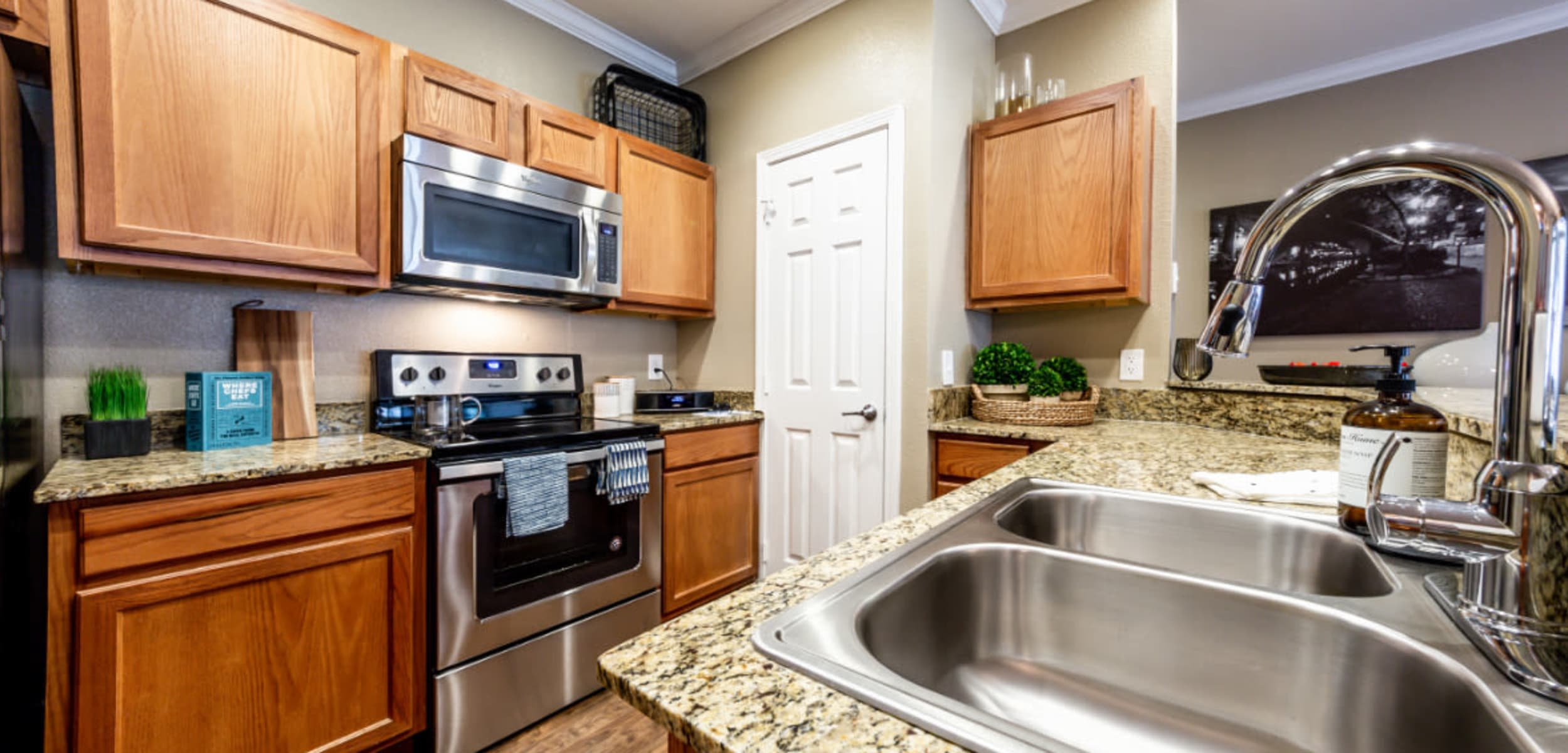Stainless steel sink with granite counters at Marquis at Stone Oak in San Antonio, Texas