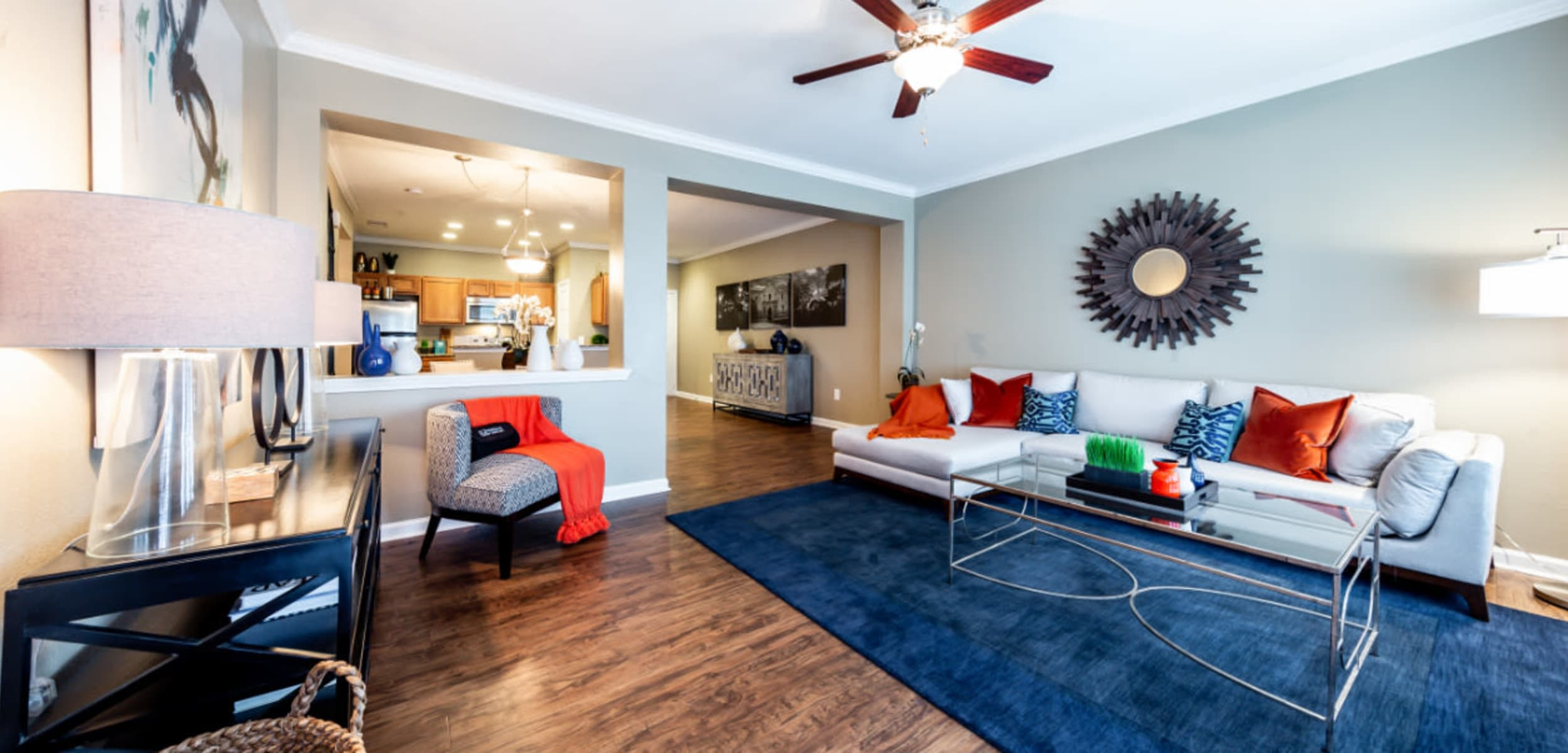 Open and bright living area with wood flooring and ceiling fan at Marquis at Stone Oak in San Antonio, Texas