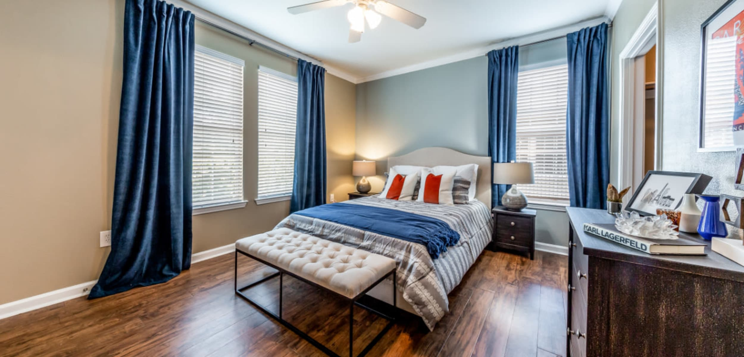 Spacious bedroom with multiple windows, ceiling fan, and wood flooring at Marquis at Stone Oak in San Antonio, Texas