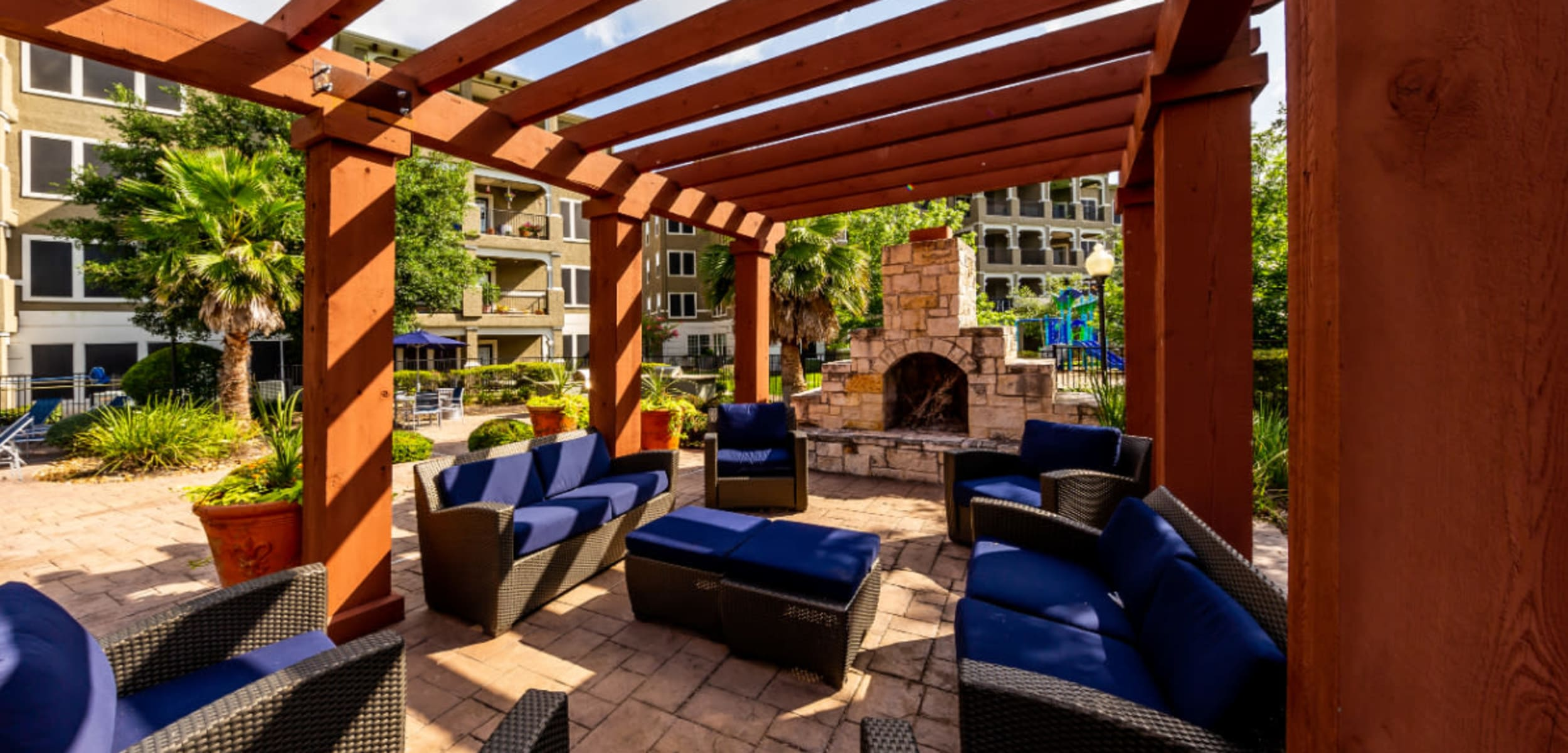 Colorful patio furniture with fireplace under gazebo at Marquis at Stone Oak in San Antonio, Texas