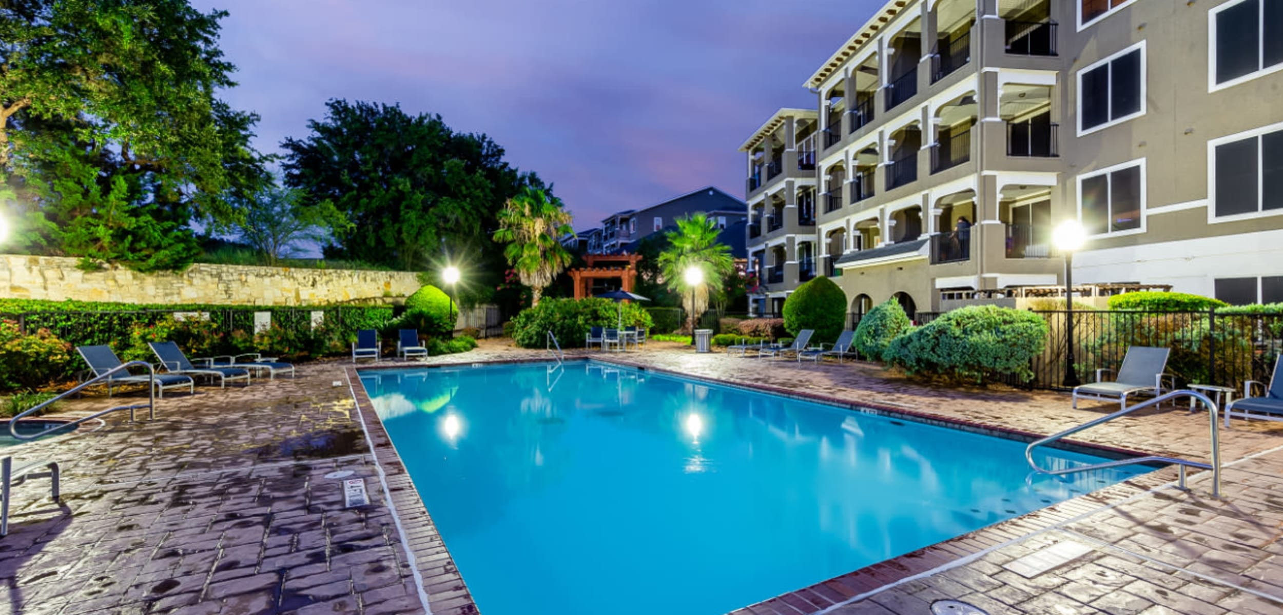Lighted pool at sunset overlooking units at Marquis at Stone Oak in San Antonio Texas,