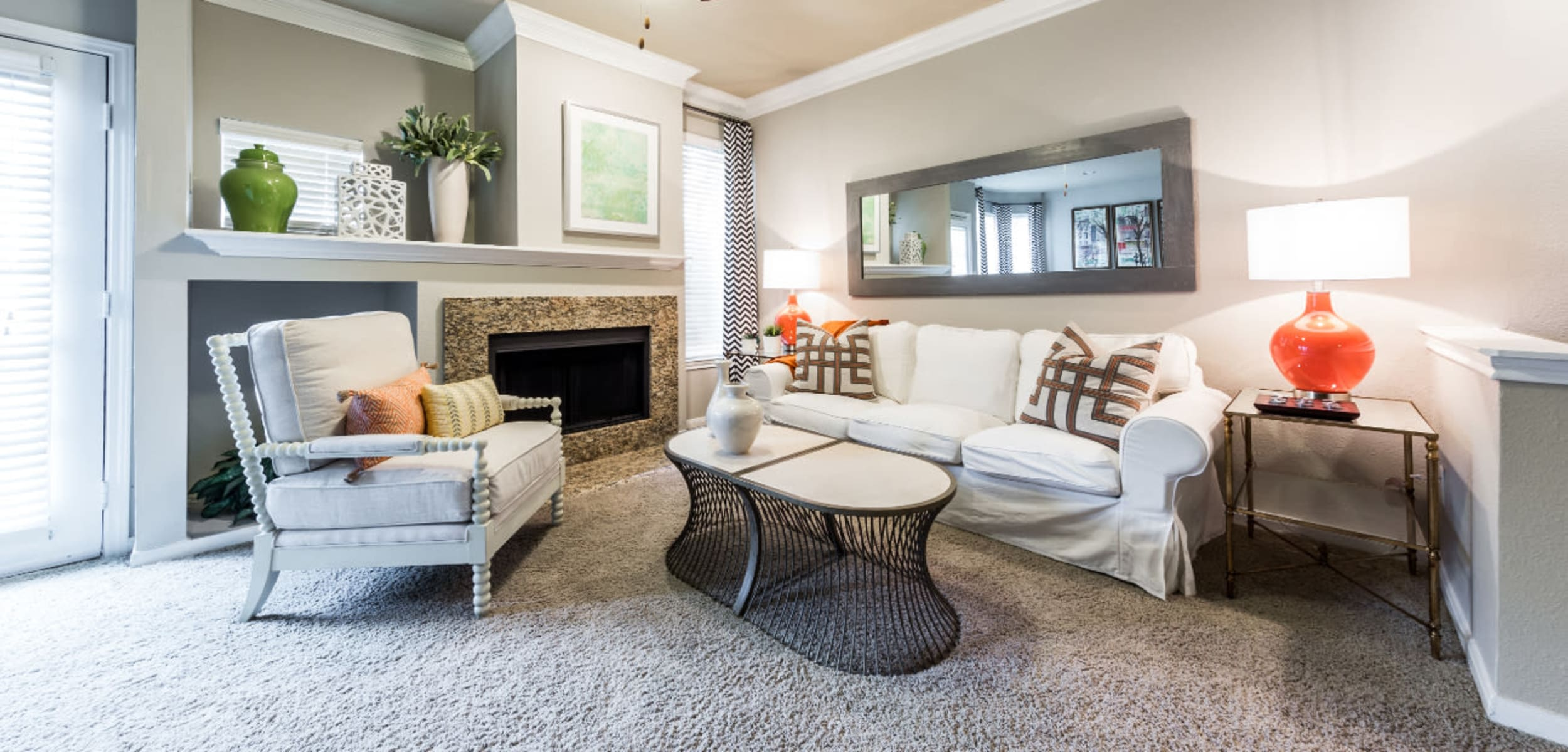 Modern carpeted living room with fireplace at Marquis at Stonegate in Fort Worth, Texas