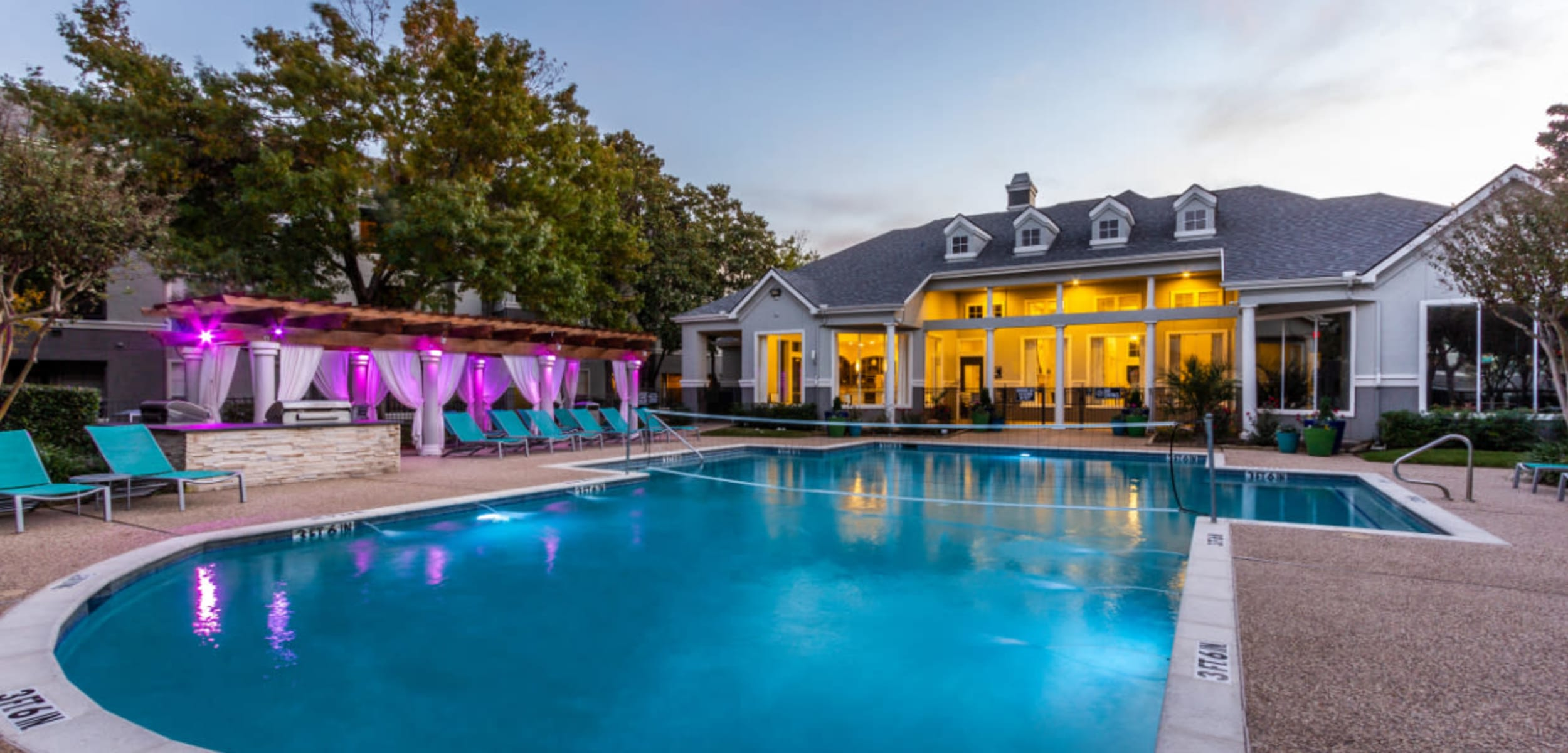 Pool with volleyball net, clubhouse, and colorful lights lounge area at sunset at Marquis at Stonegate in Fort Worth Texas,