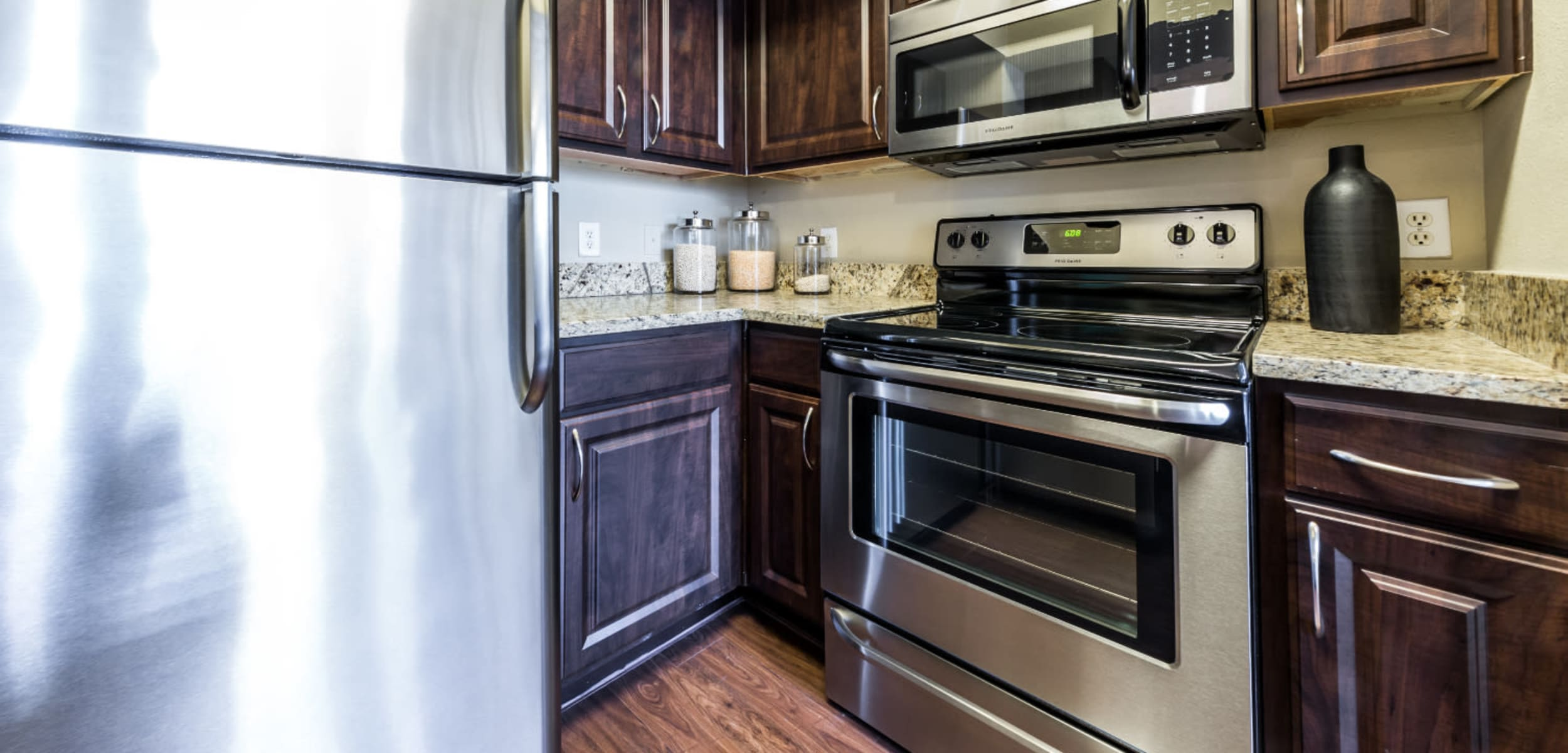 Modern kitchen with stainless steel appliances and granite counter tops at Marquis at Stonegate in Fort Worth, Texas