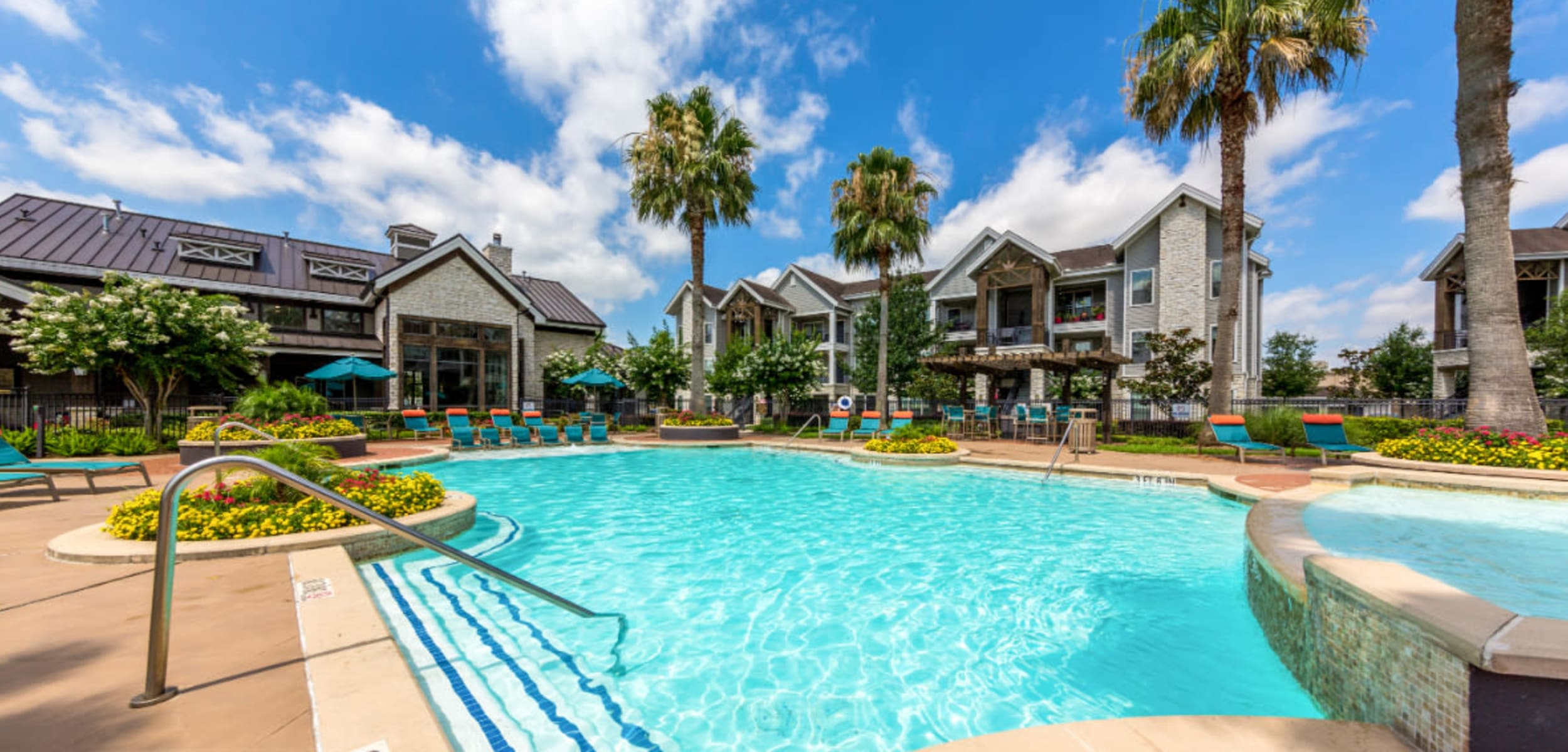 Resort style swimming pool surounded by lounge chairs at Marquis at Sugar Land in Sugar Land, Texas