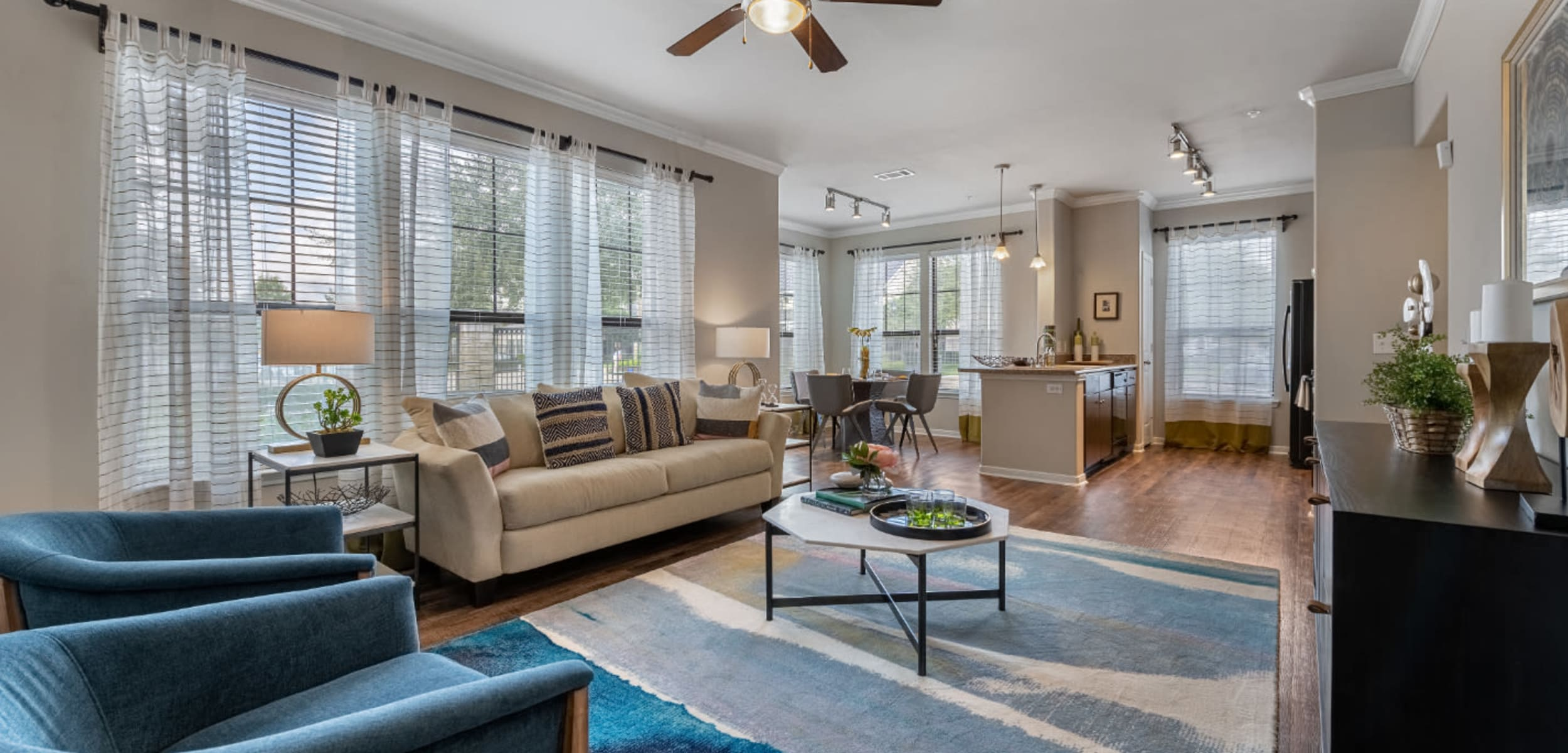 Spacious and comfortable living area overlooking kitchen and dining area at Marquis at Sugar Land in Sugar Land, Texas