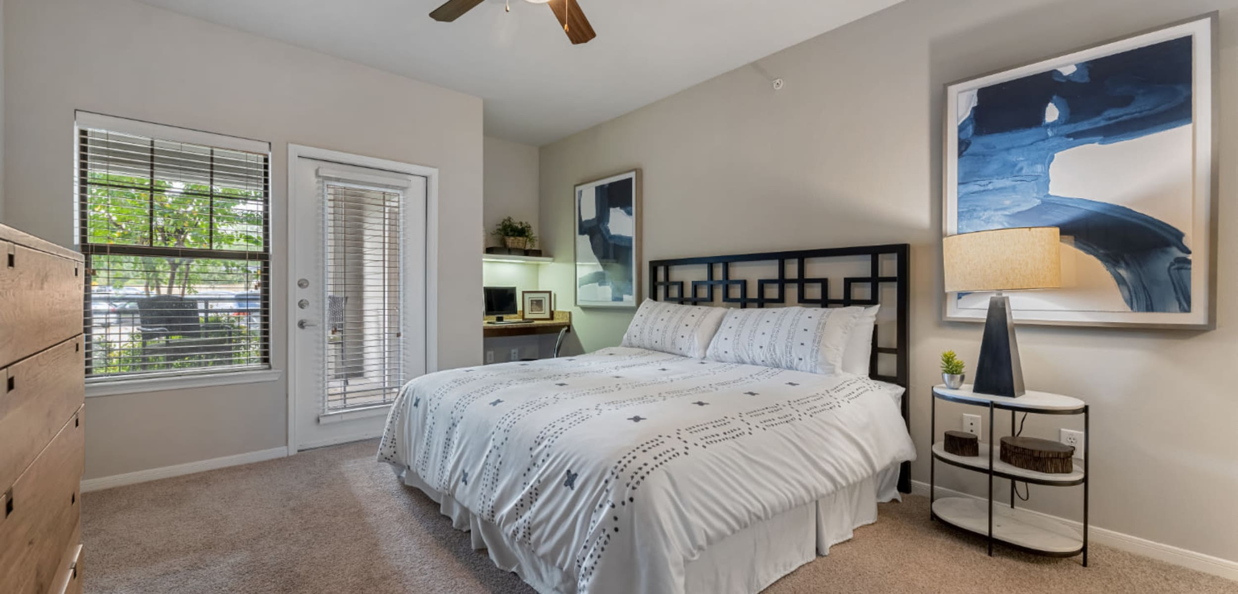 Spacious bedroom with computer nook and access to private balcony at Marquis at Sugar Land in Sugar Land, Texas