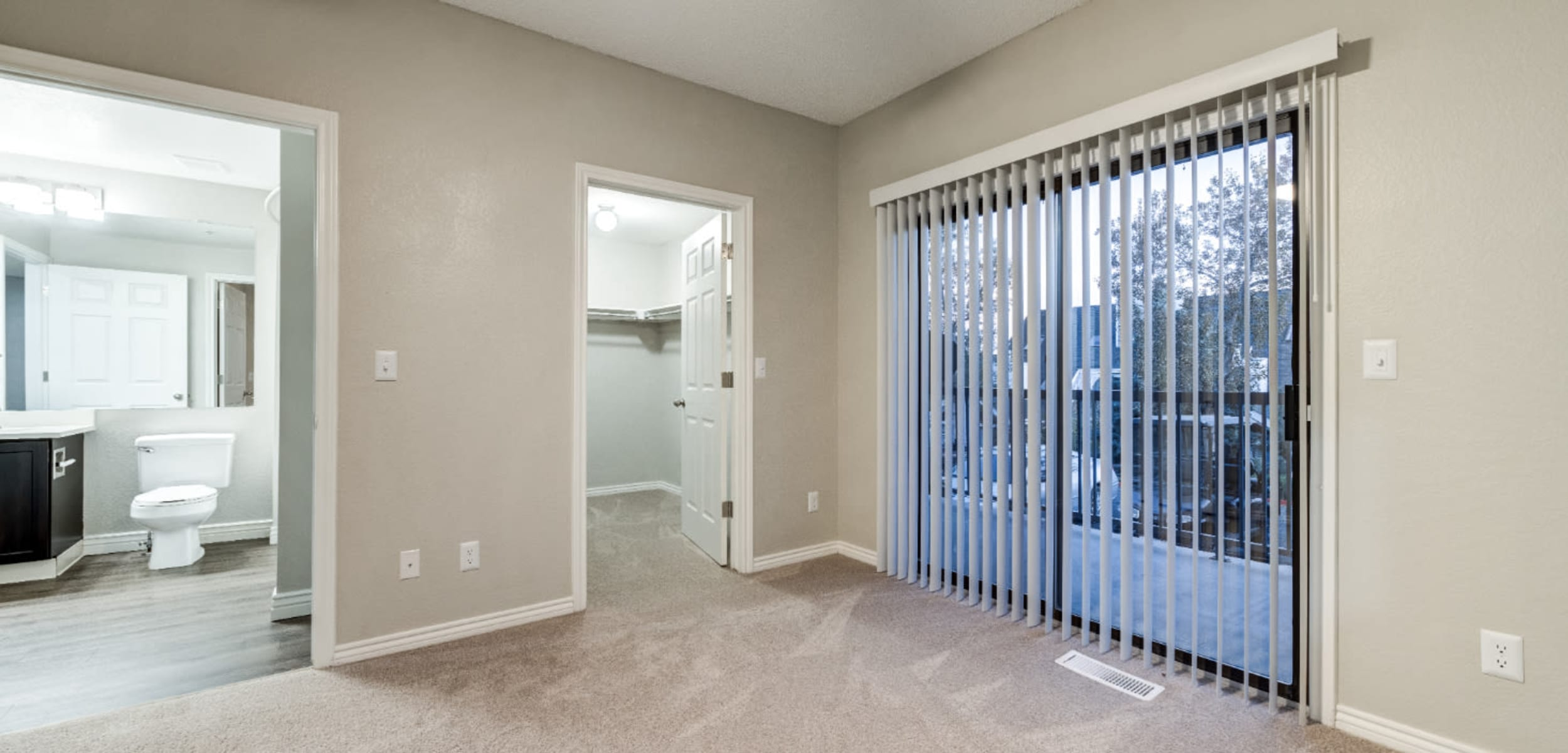 Carpeted master bedroom with walk-in closet, bathroom, and private access to balcony at Ashford Belmar in Lakewood, Colorado