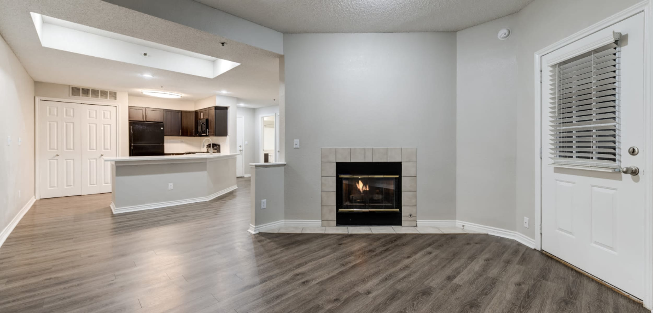 Spacious living area with wood flooring and fireplace at Ashford Belmar in Lakewood, Colorado