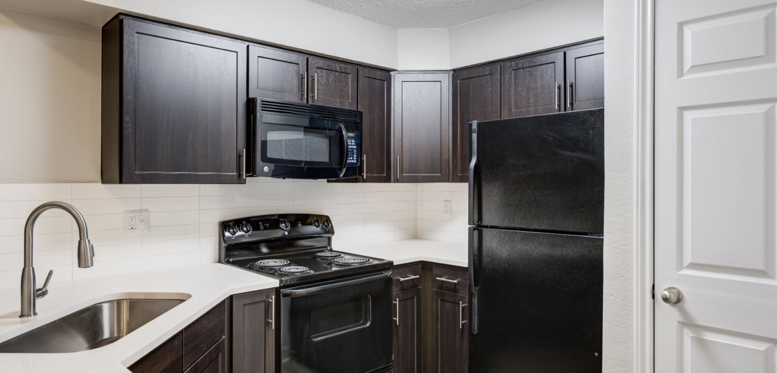 Unit kitchen with granite counters and wood flooring at Ashford Belmar in Lakewood, Colorado