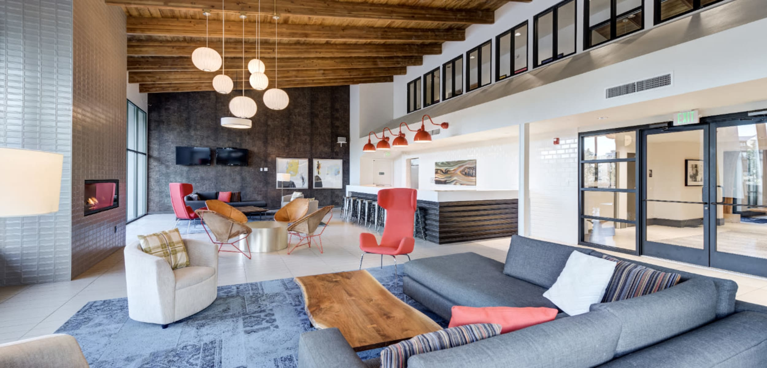 Bright and open community clubhouse with lounge area and fireplace at Ashford Belmar in Lakewood, Colorado