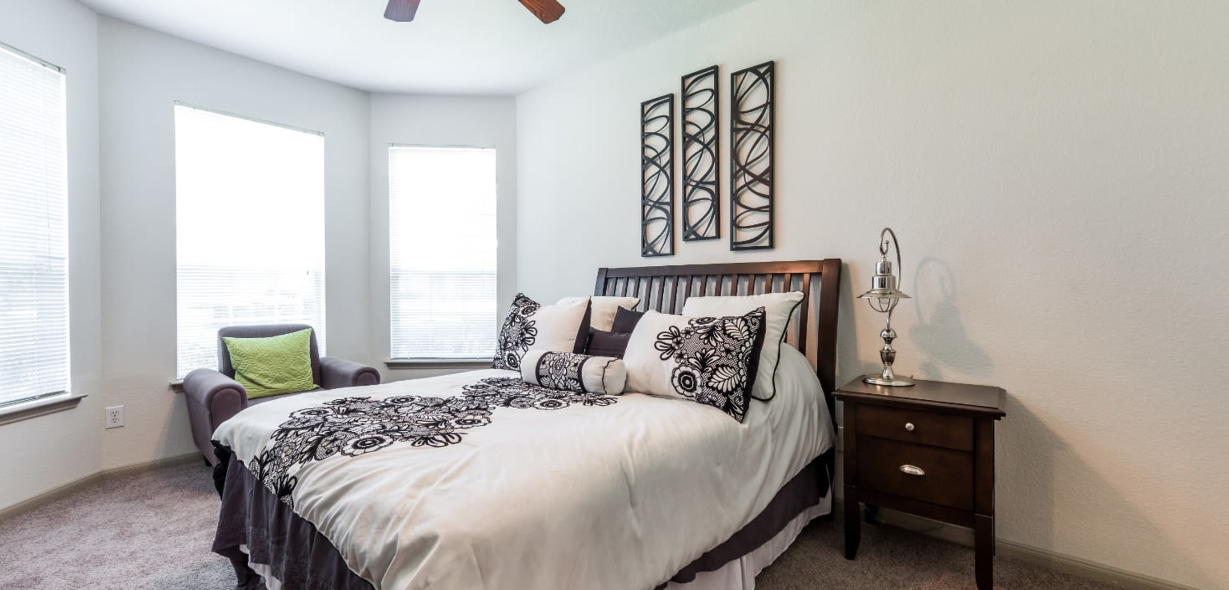 Carpeted bedroom with multiple windows at Marquis at Clear Lake in Webster, Texas
