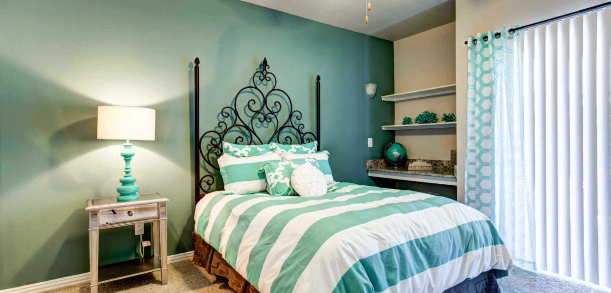 Modern style bedroom with built in shelves area and door to private balcony at Marquis at Silver Oaks in Grapevine, Texas