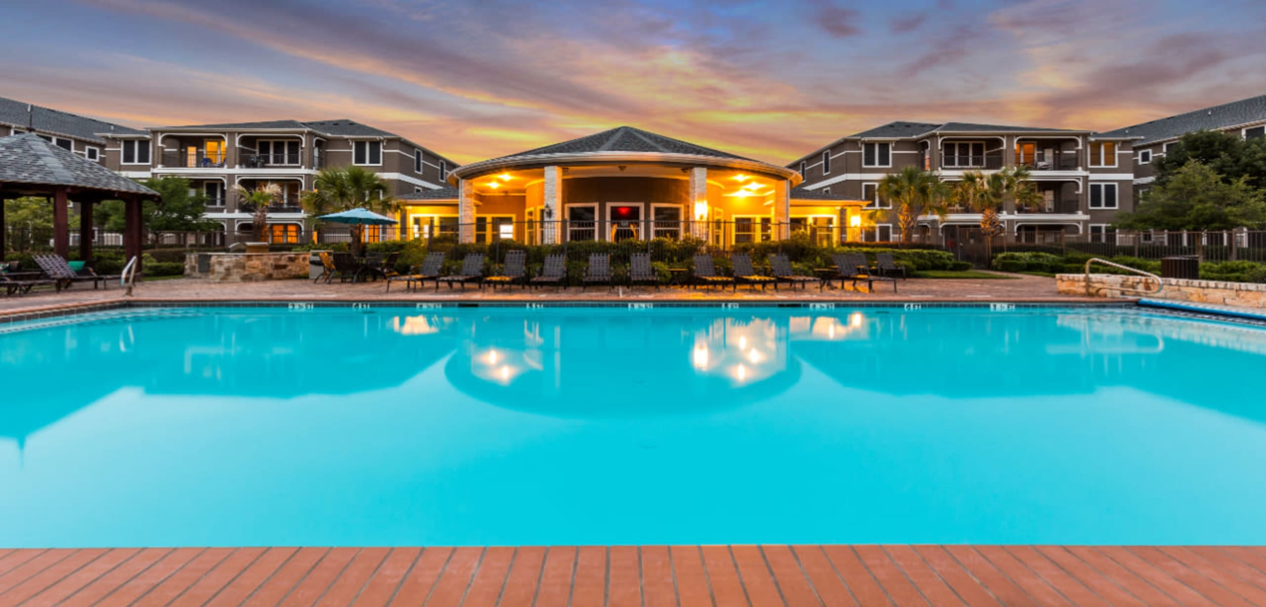 Sparkling pool facing clubhouse at sunset at Marquis at The Cascades in Tyler Texas,