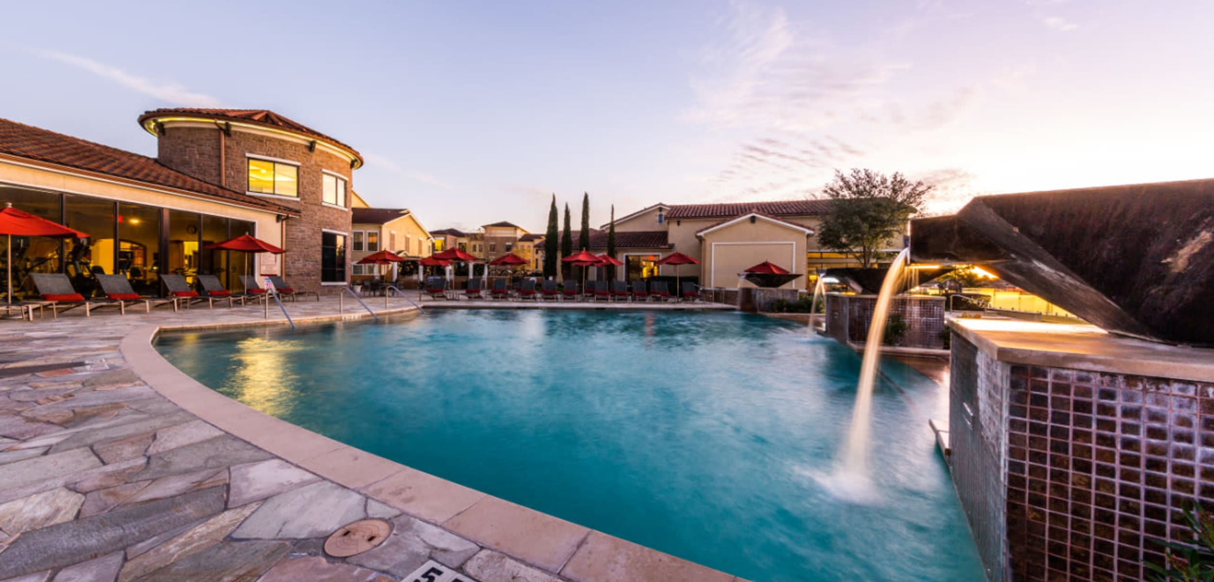 Sparkling pool with waterfall feature at Marquis at the Reserve in Katy Texas,
