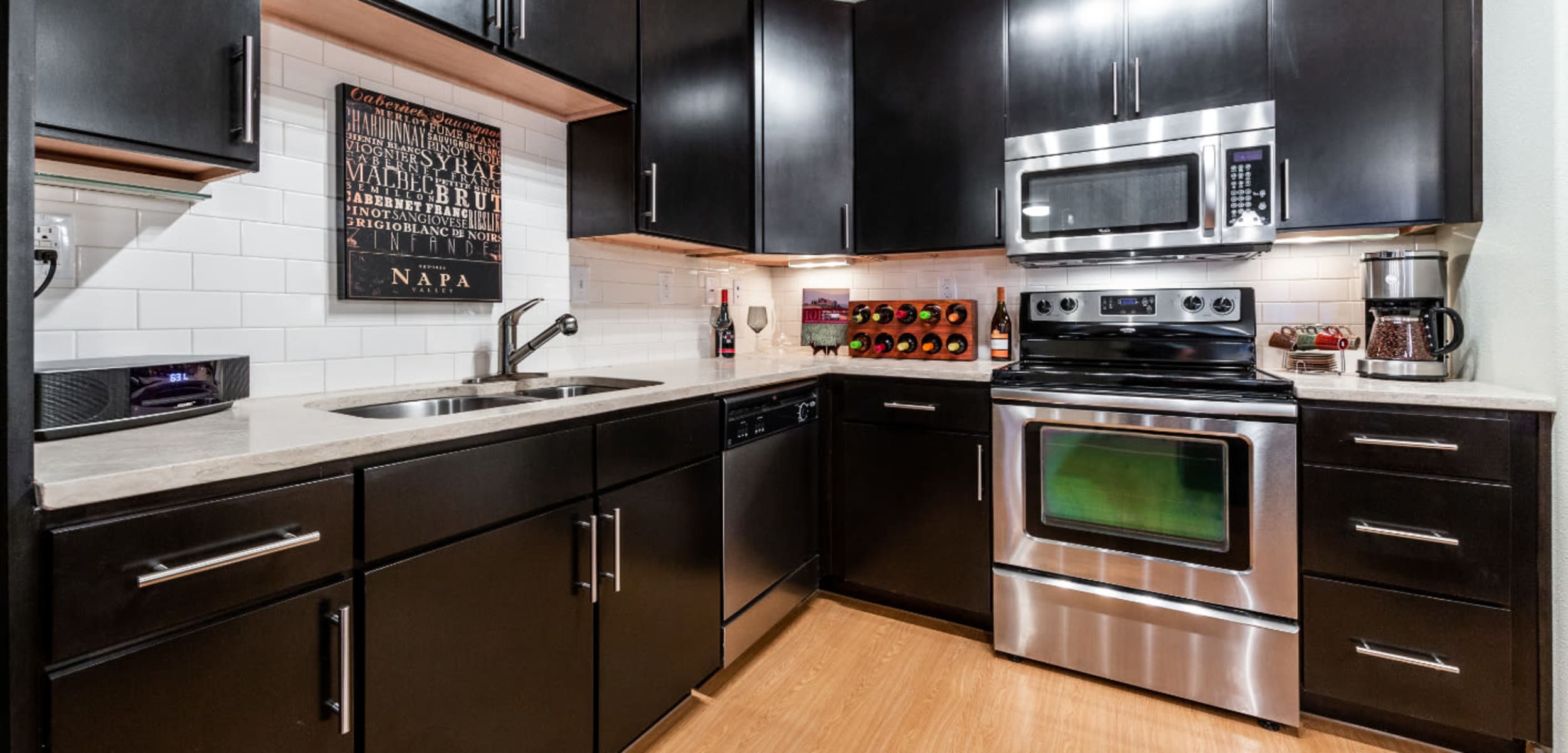 Modern style kitchen with stainless steel appliances at Marquis at the Reserve in Katy, Texas