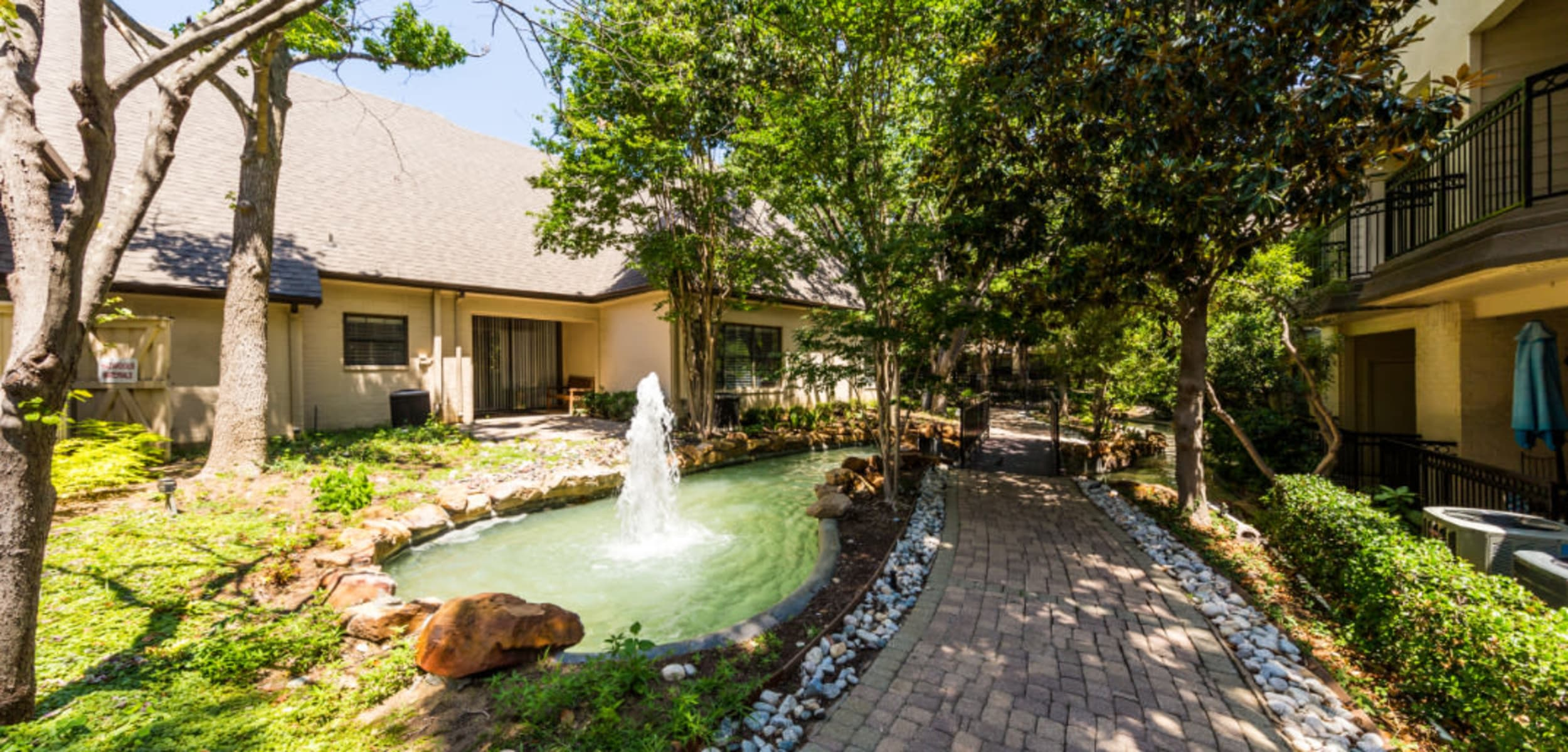 Brick walking path next to water feature pond between unit buildings at Marquis at Waterview in Richardson, Texas