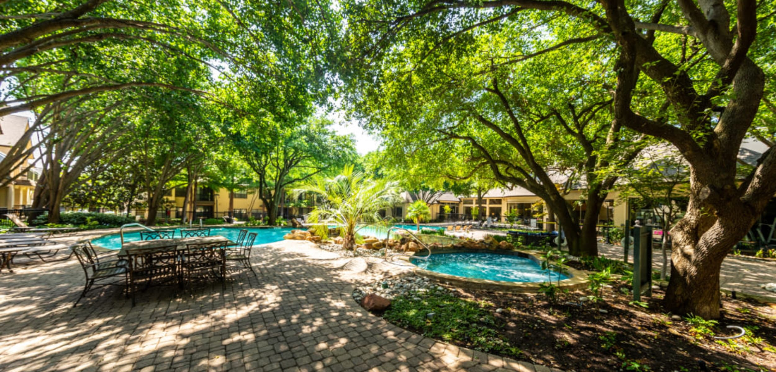Pool deck area with tables and chairs covered by lush trees at Marquis at Waterview in Richardson Texas,