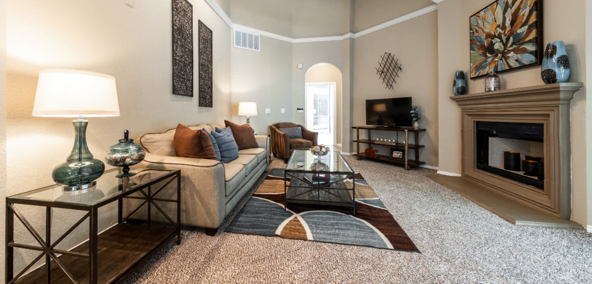 Spacious and carpeted living room with vaulted ceilings and fireplace at Marquis at Waterview in Richardson, Texas