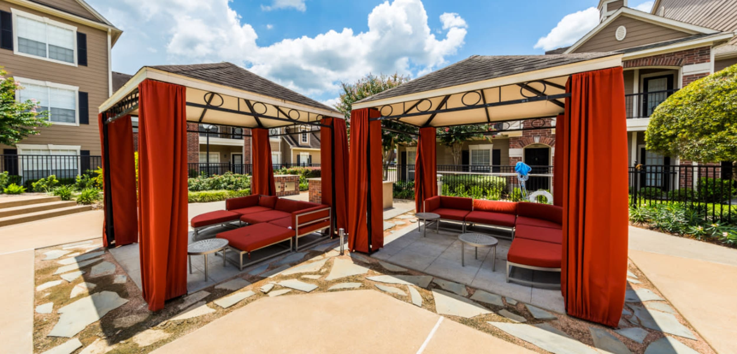 Gazebos with lounge couches and side tables at Marquis on Park Row in Houston, Texas