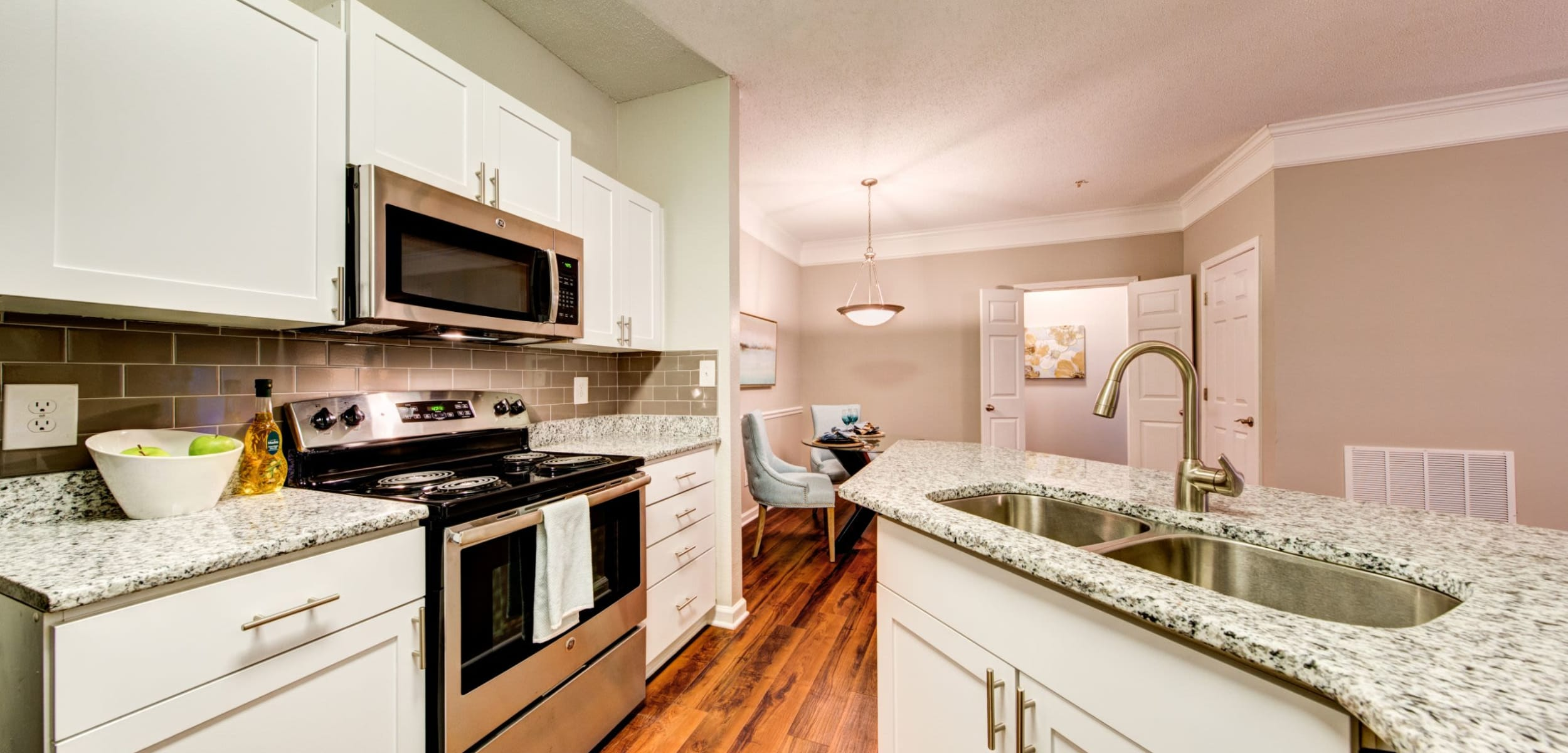 Modern kitchen with white cabinets and stainless steel appliances at Marquis on Edwards Mill in Raleigh, North Carolina