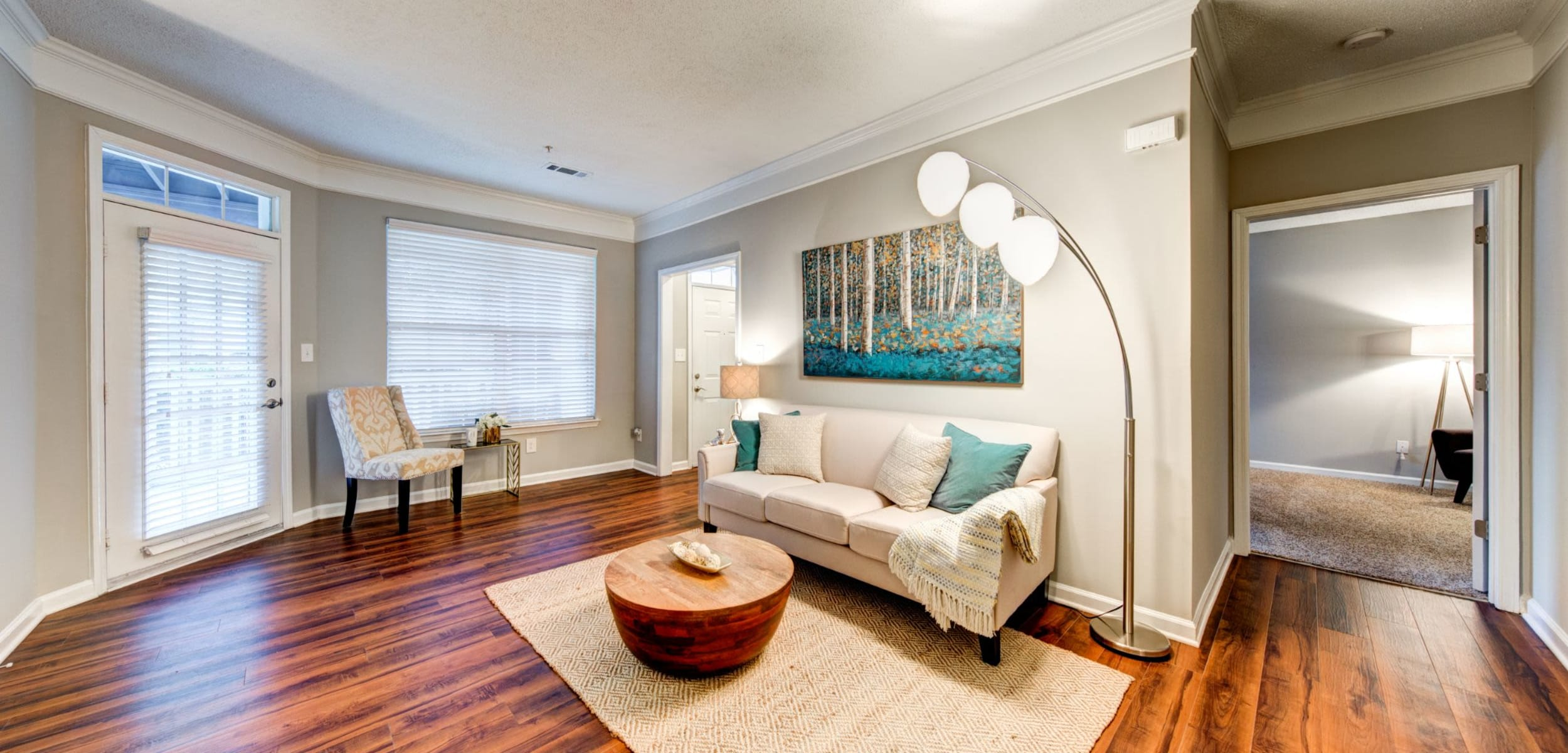 Bright living room with multiple windows and wood floors at Marquis on Edwards Mill in Raleigh, North Carolina