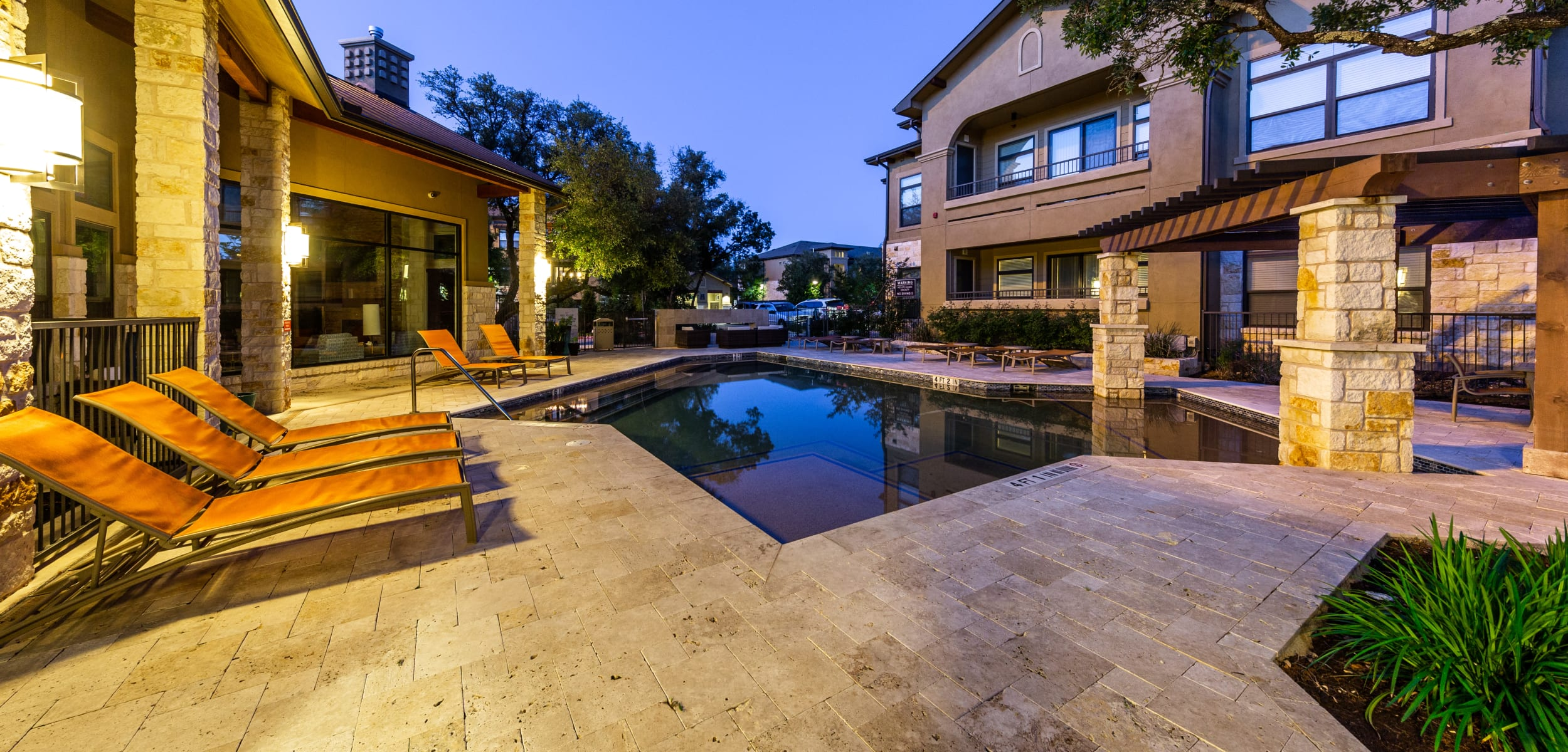Outdoor pool at sunset with lounge chairs at Marquis at Barton Trails in Austin Texas,